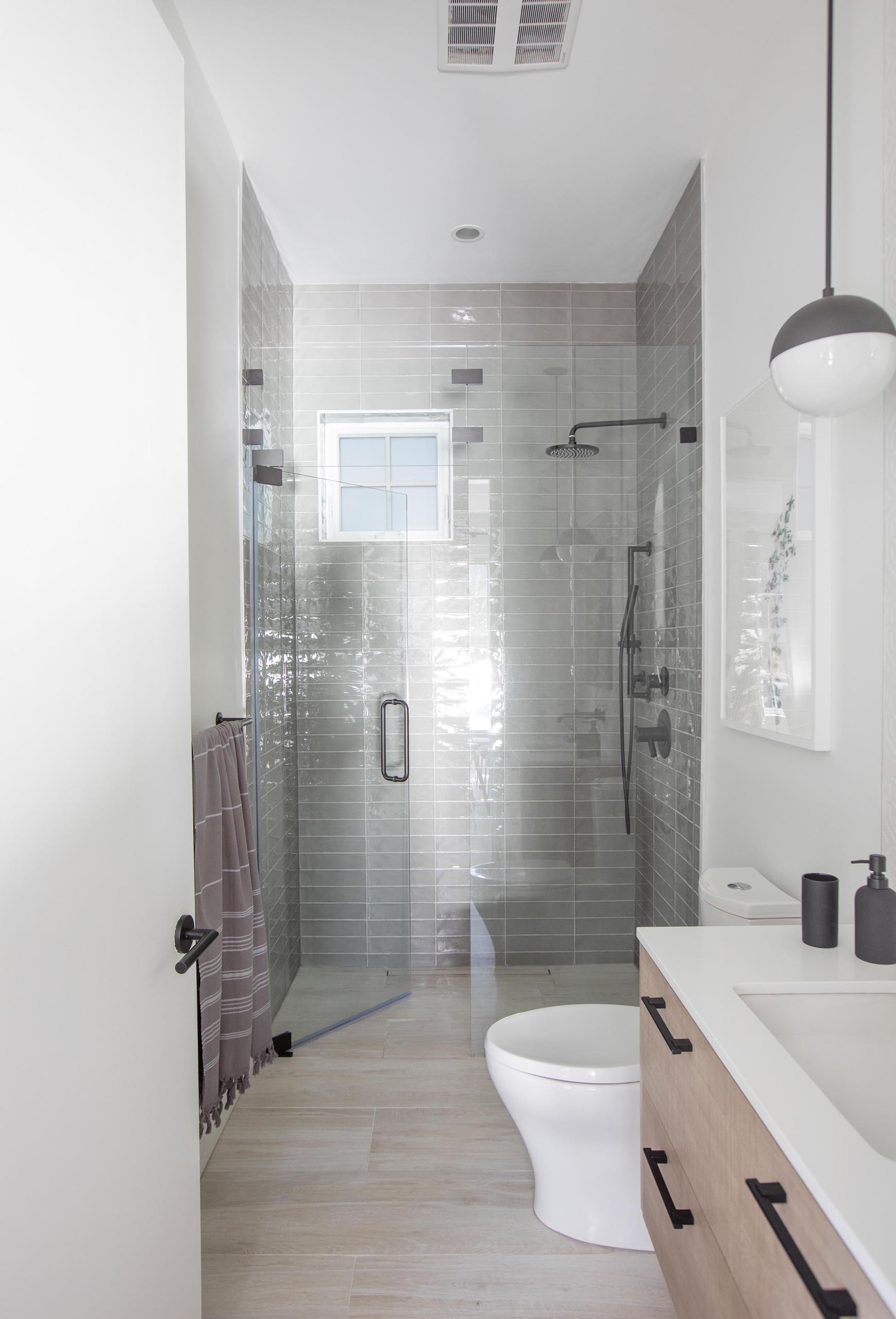 A modern bathroom that includes a wood vanity with a white countertop, and a shower lined with floor-to-ceiling gray tiles.
