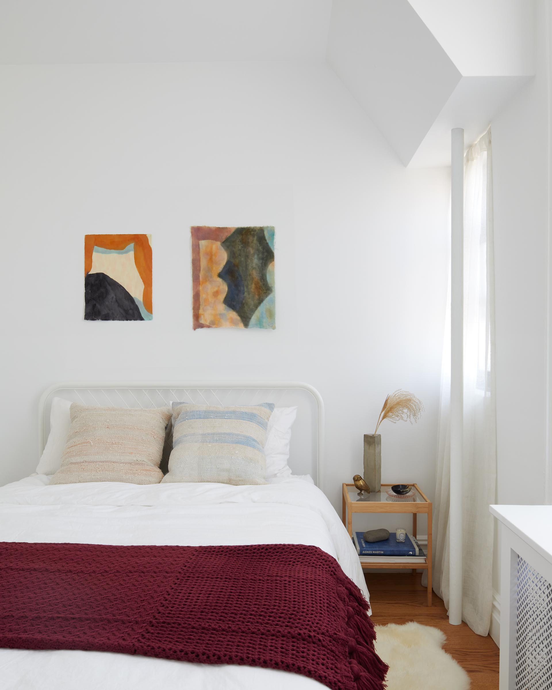 In this guest bedroom, bright and colorful accents stand out against the light-colored walls.