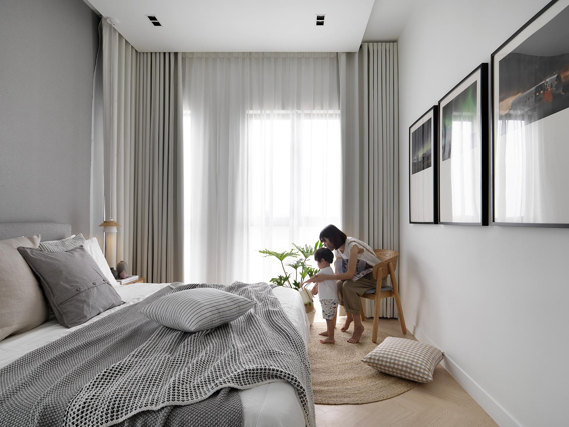 Herringbone wood flooring, neutral colors, natural fibers, and plants create a calm environment for the bedroom.