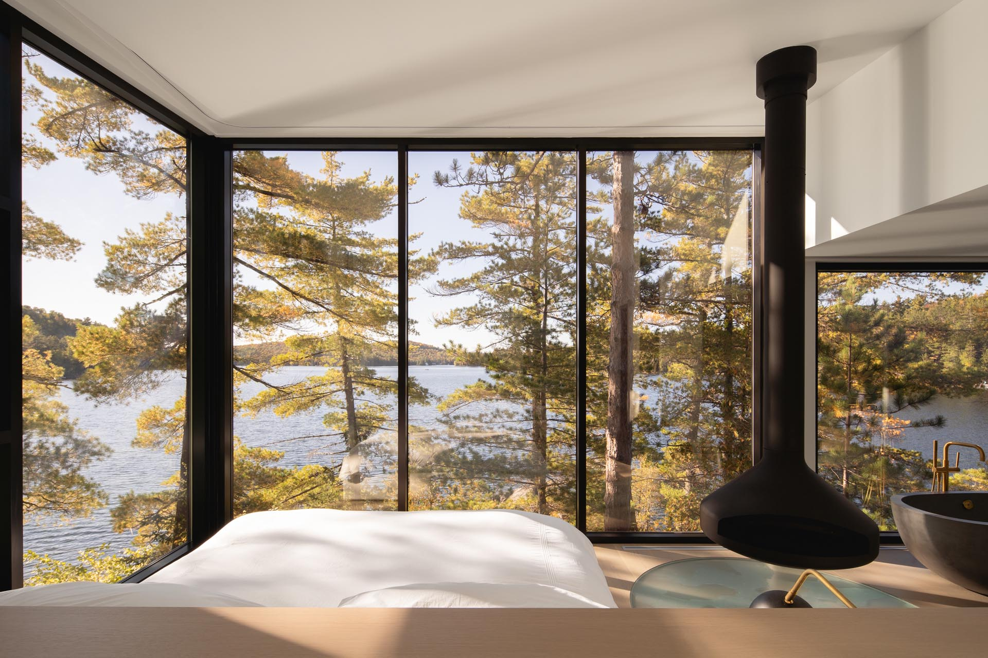 A modern master bedroom with floor-to-ceiling windows, a suspended black fireplace, and a freestanding bathtub.