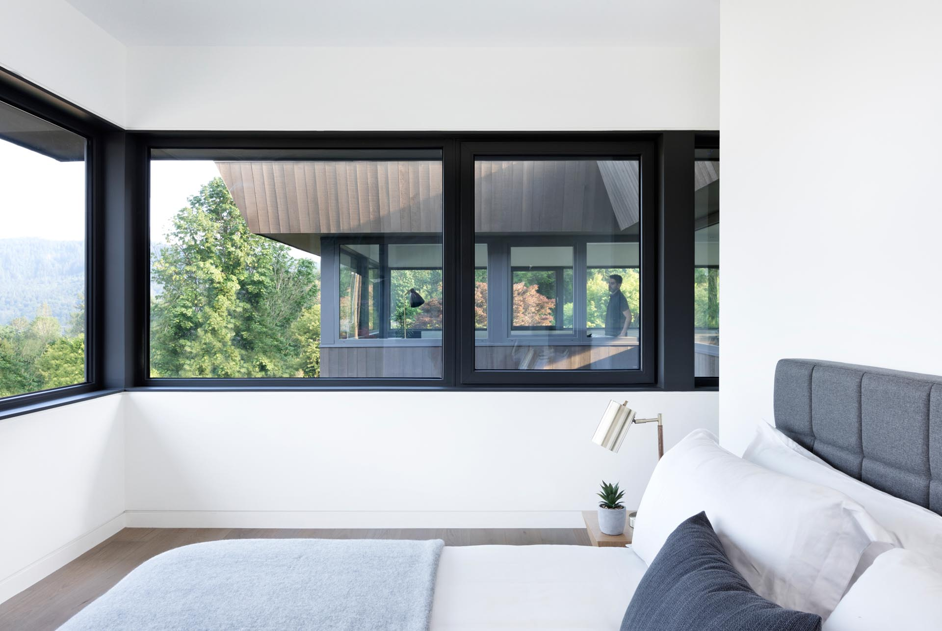A modern bedroom with wrap around windows.