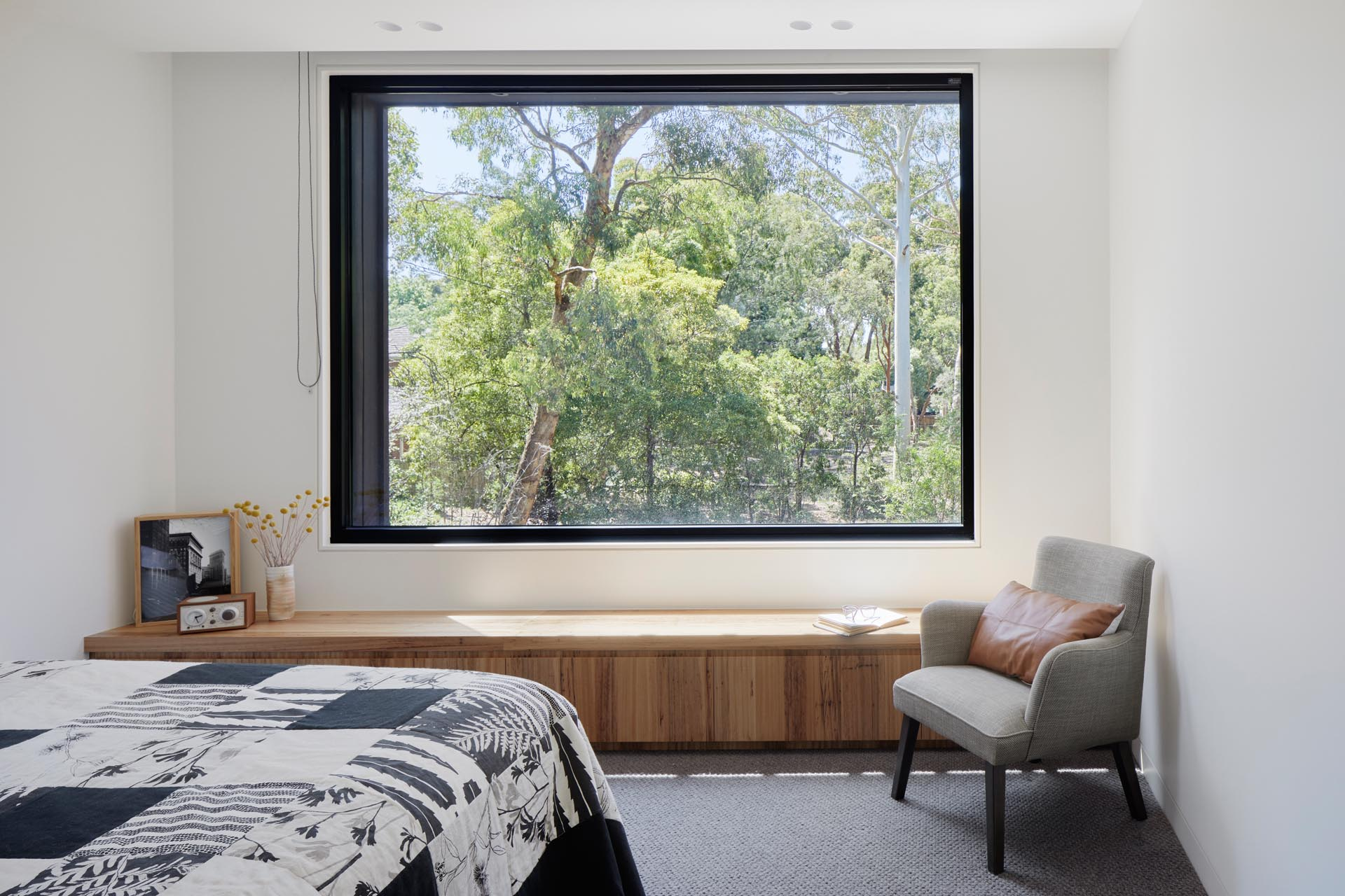 In this modern bedroom, a large window offers views of the gum trees outside, while plush wool carpet helps to absorb sound for privacy.