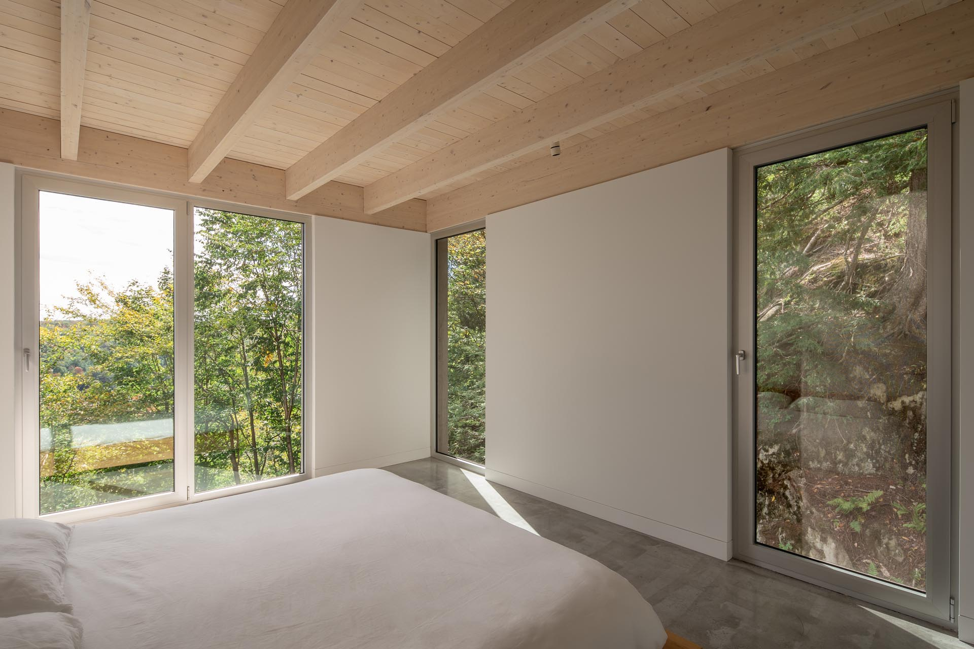 A master bedroom suite with minimal furniture has tall windows that frame the trees and rocks outside.