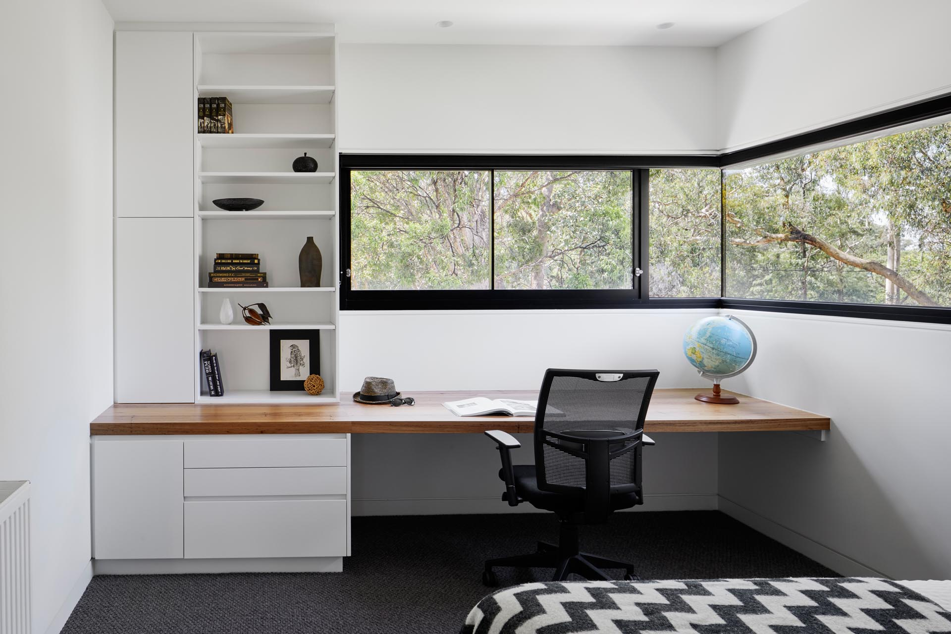 In this modern bedroom, there's wrap-around windows and a built-in wood desk with drawers, cabinets, and shelving.