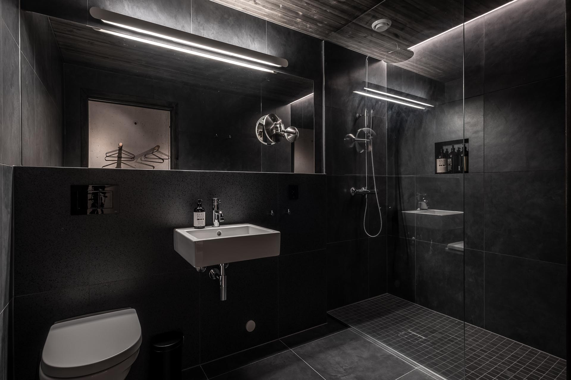 In this dark bathroom, large format black tiles and lighting have been used to create a dramatic appearance.