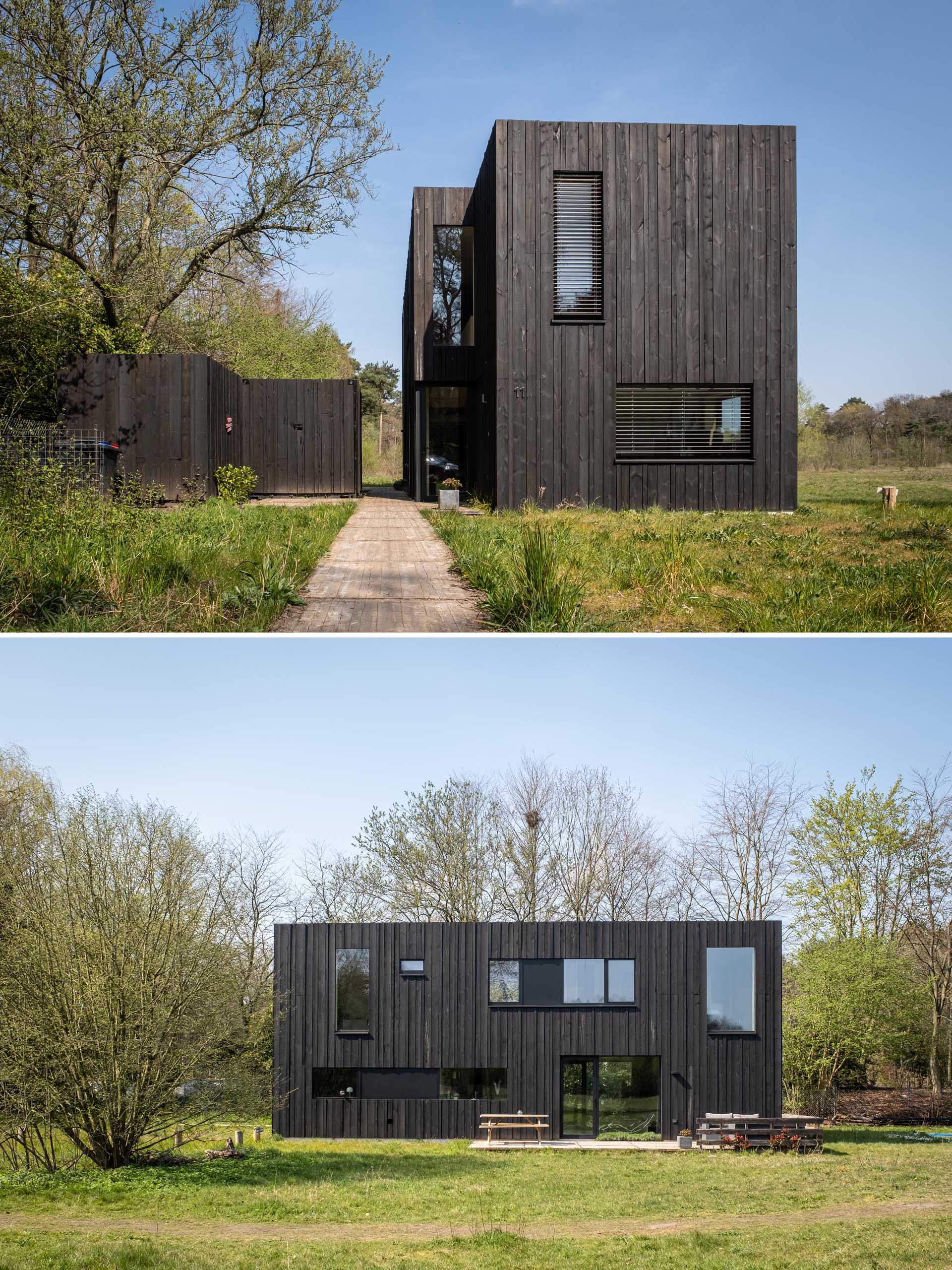 A modern prefab home with black wood siding, black window frames, and a separate shed.