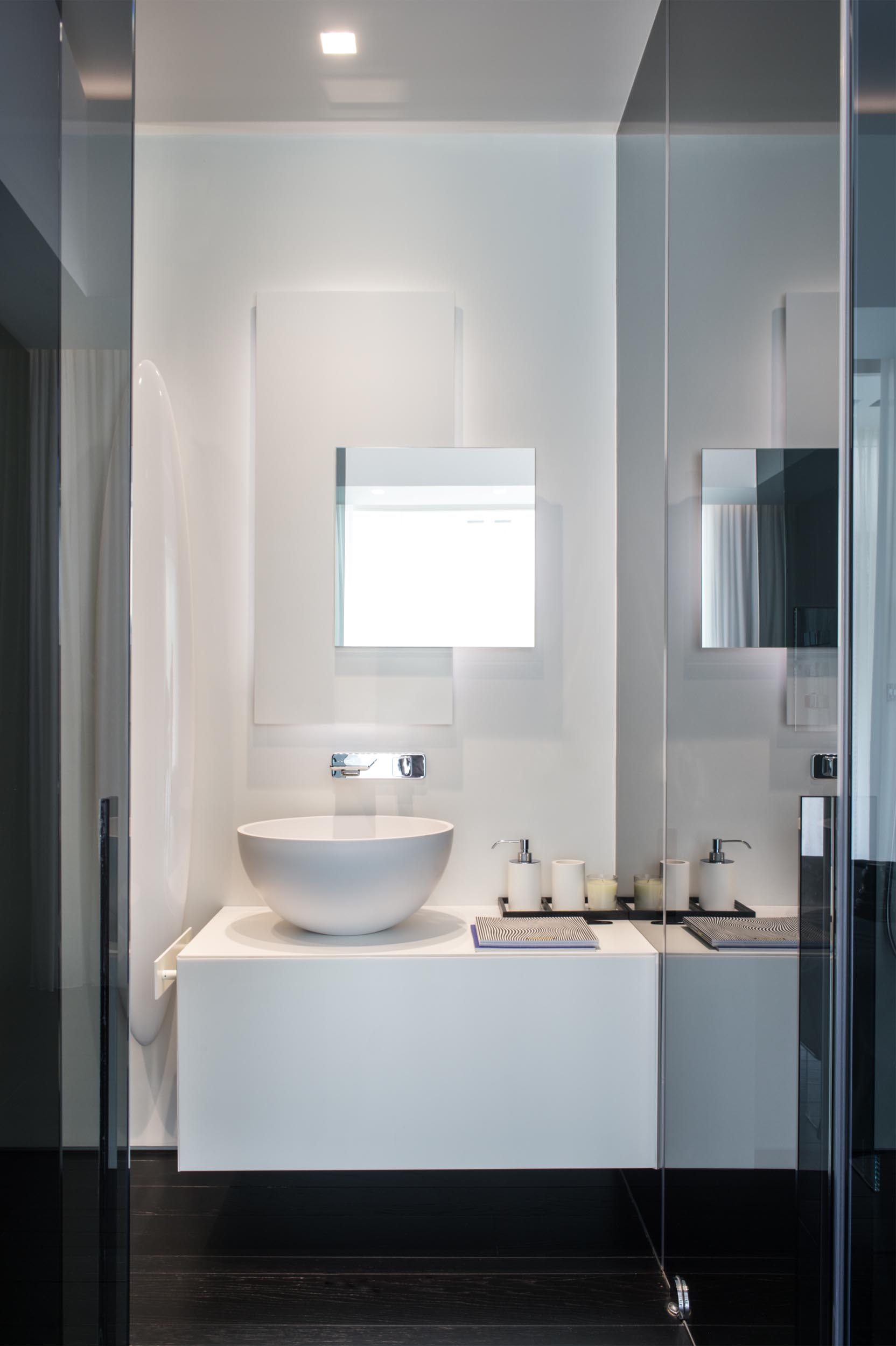 A modern bathroom with a white vanity and backlit mirror, and contrasting black floor.