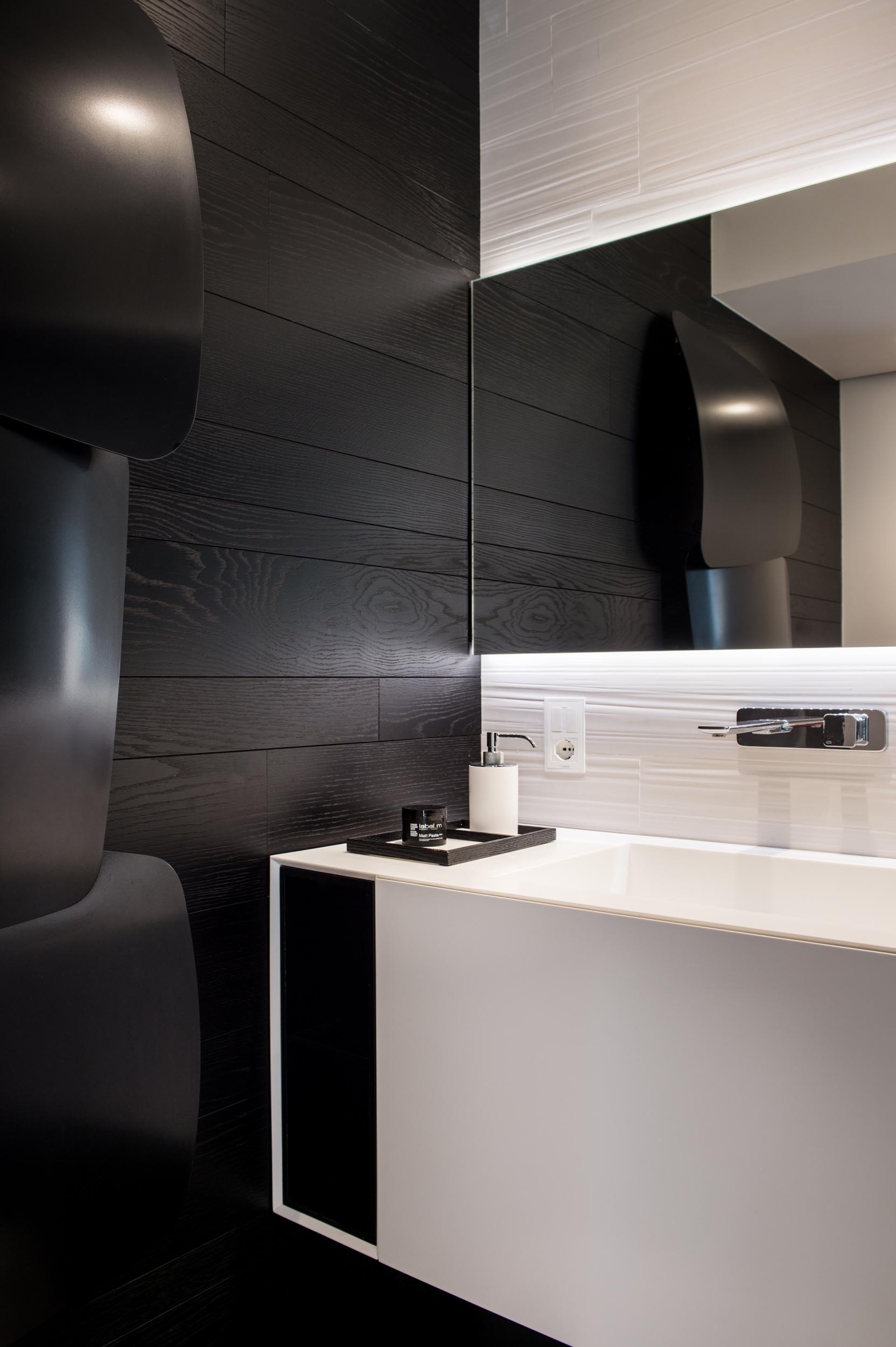 A modern bathroom with a white vanity and backlit mirror, and a contrasting black accent wall.