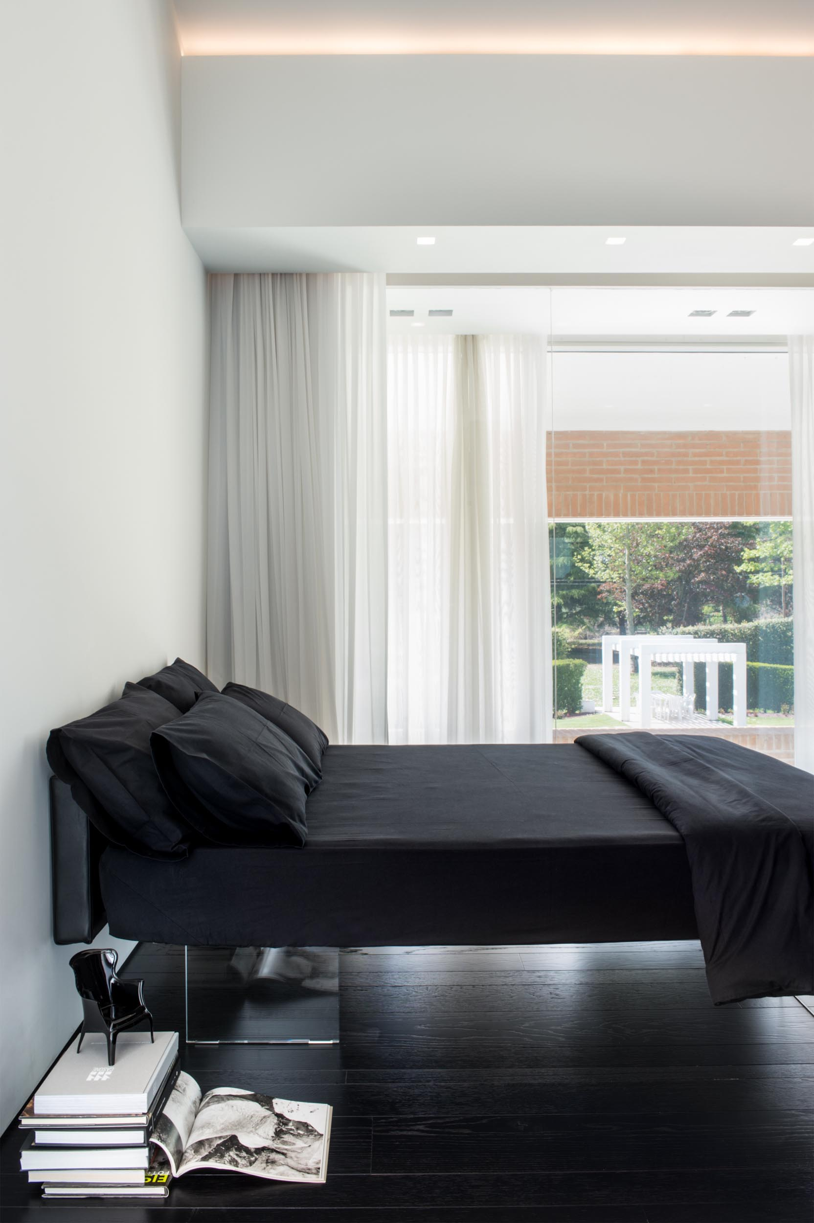 A modern bedroom with a clear bed frame that gives the appearance of a floating bed.