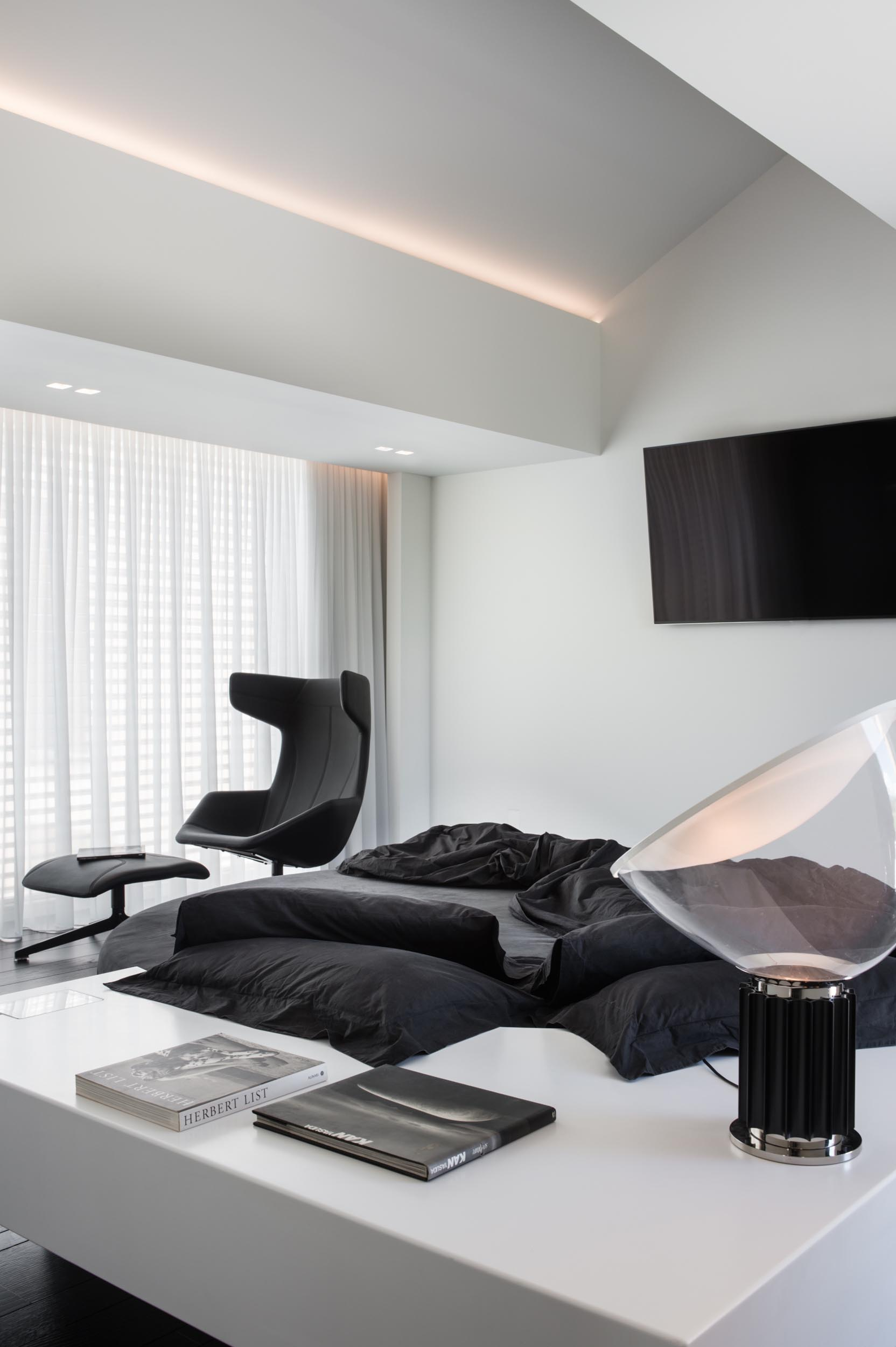A modern bedroom with a black and white color theme.