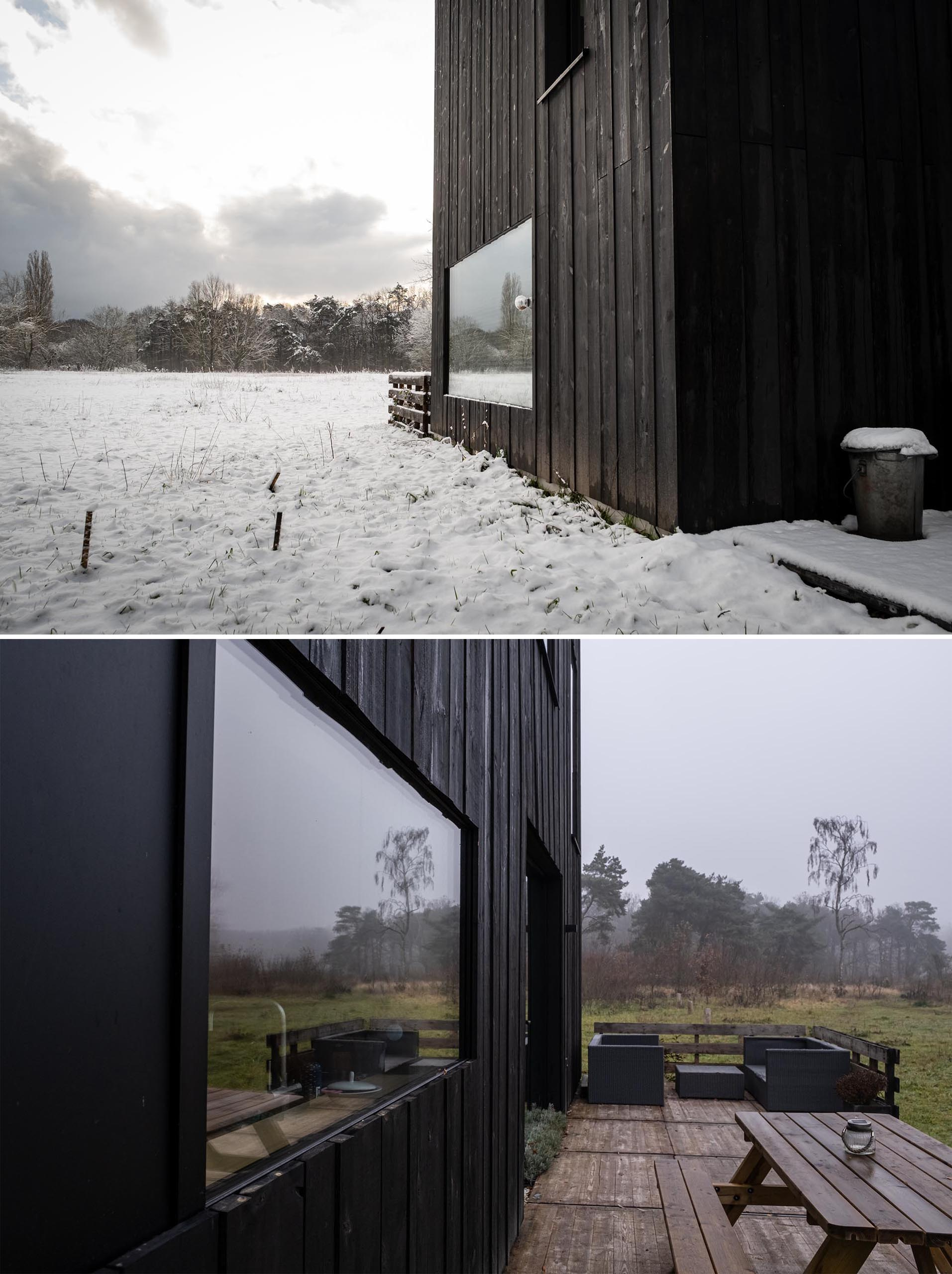 A modern prefab home with black wood siding and matching matte black window frames.