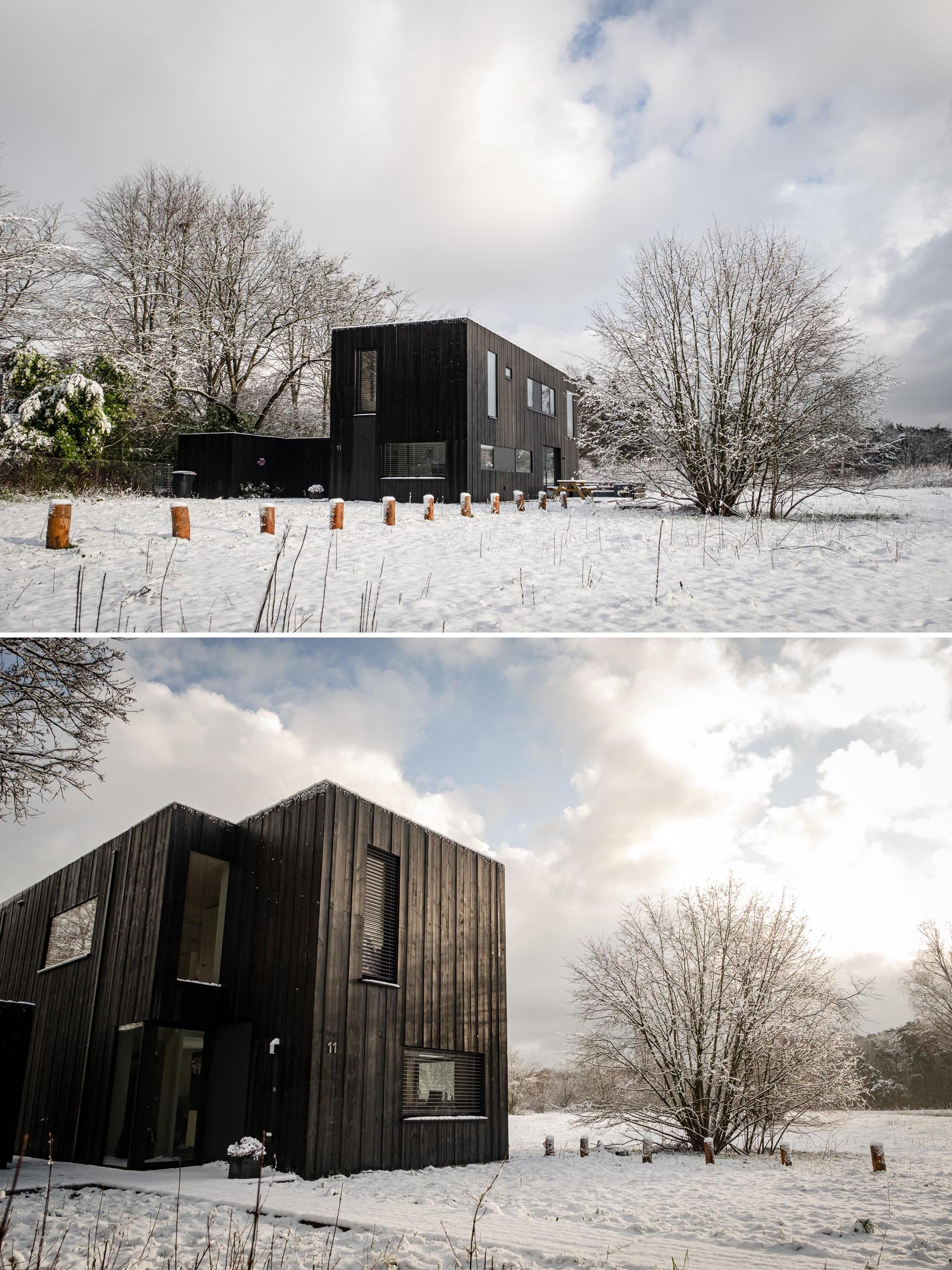A modern prefab home with black weathered wood siding and black window frames.