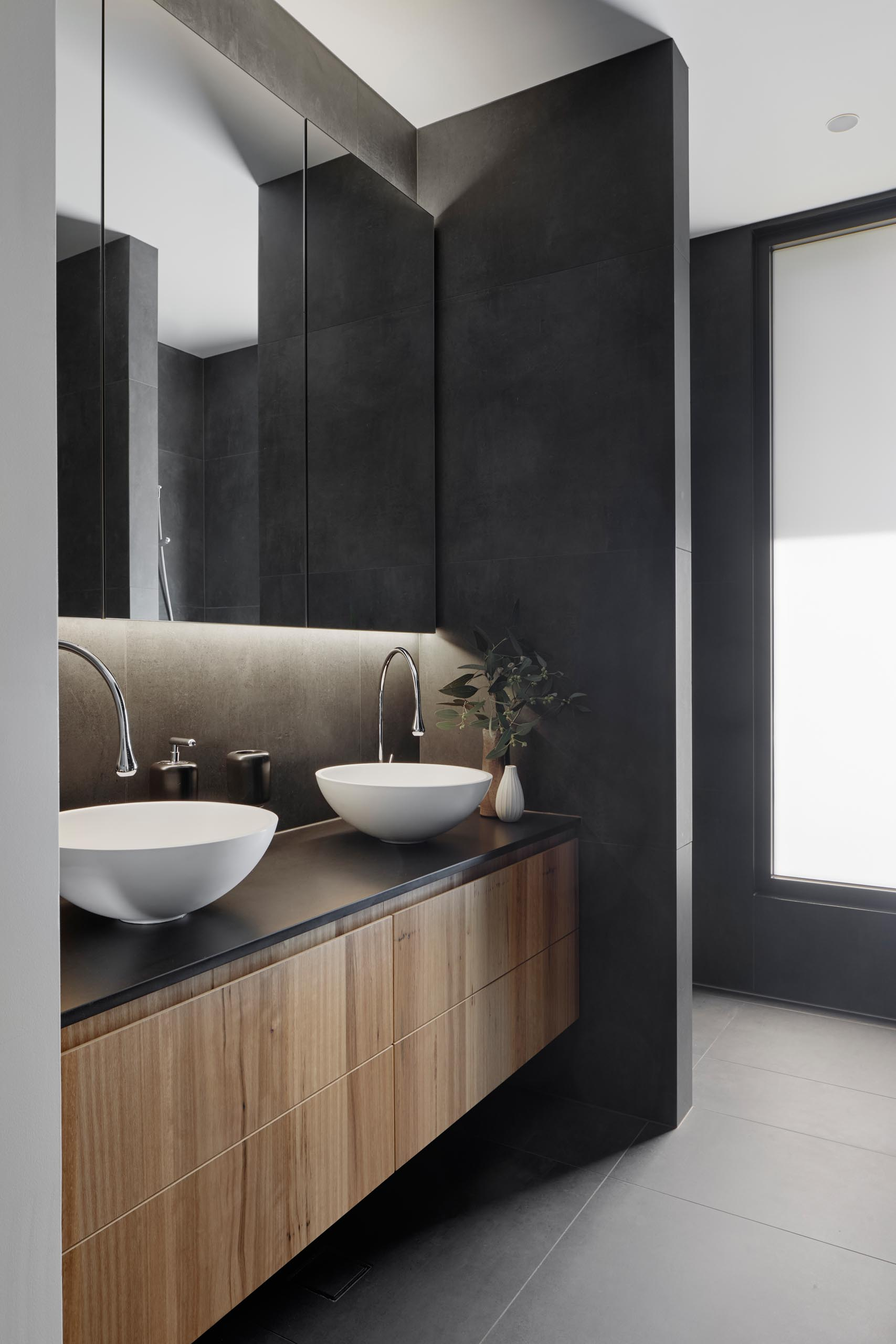 In this modern bathroom, dark gray walls and floors are combined with a wood vanity, white basins, and a backlit mirror.