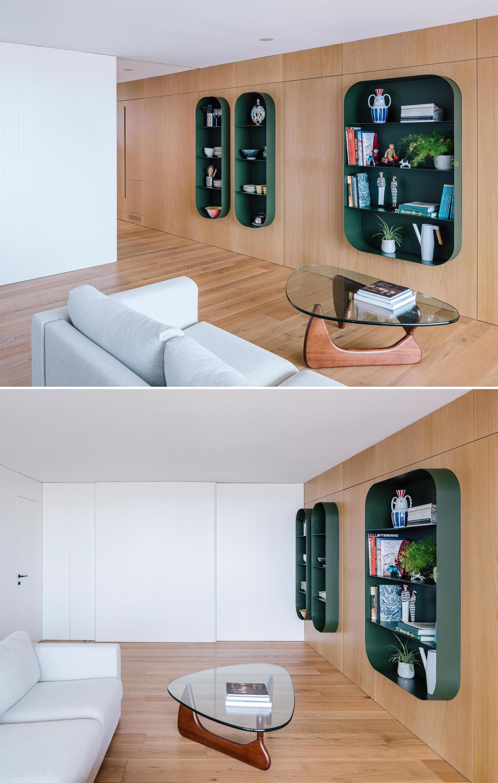 A wood wall that includes hidden storage and partially embedded dark green shelves.