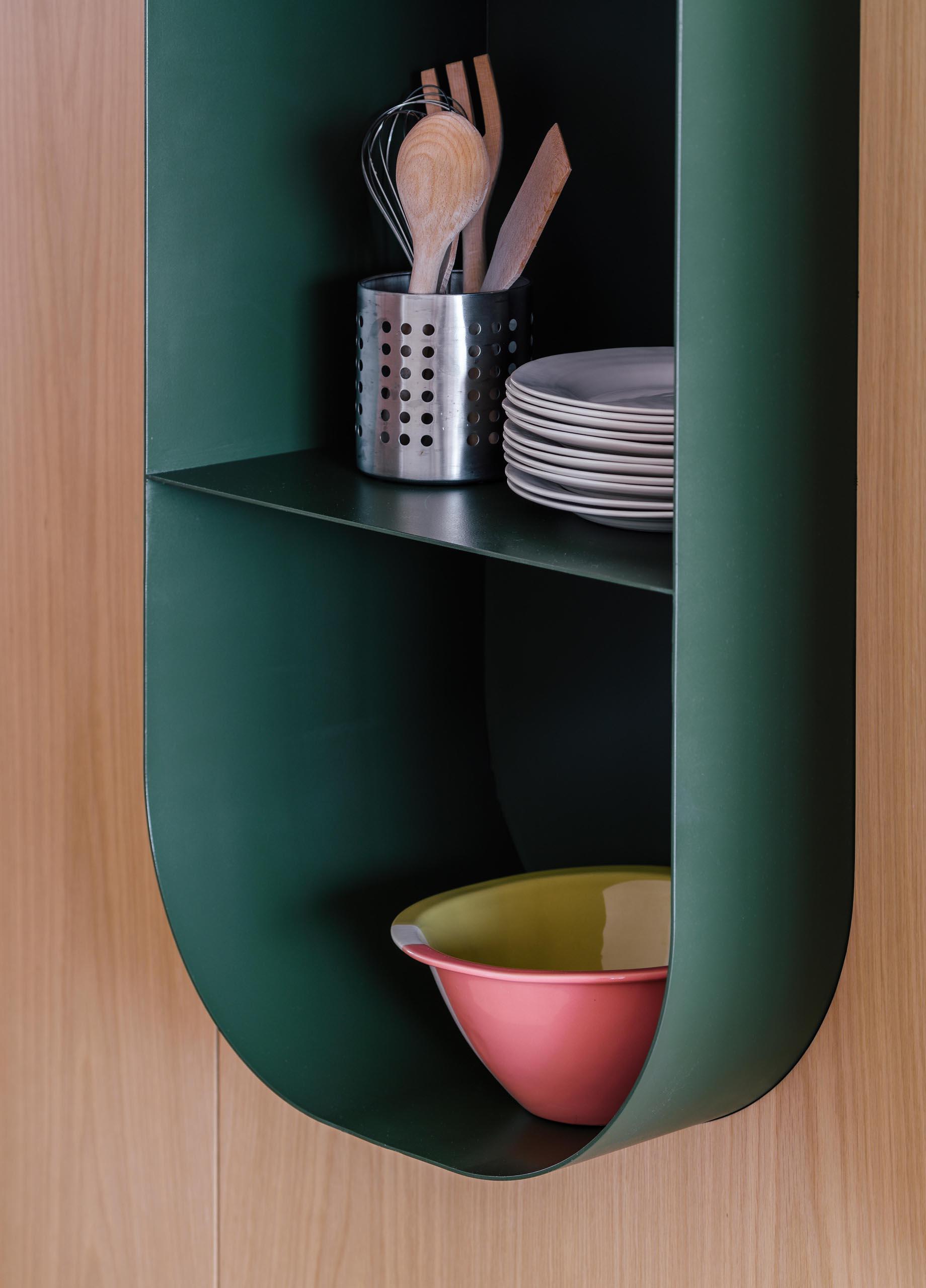 A modern dark green wall shelf with a curved design.