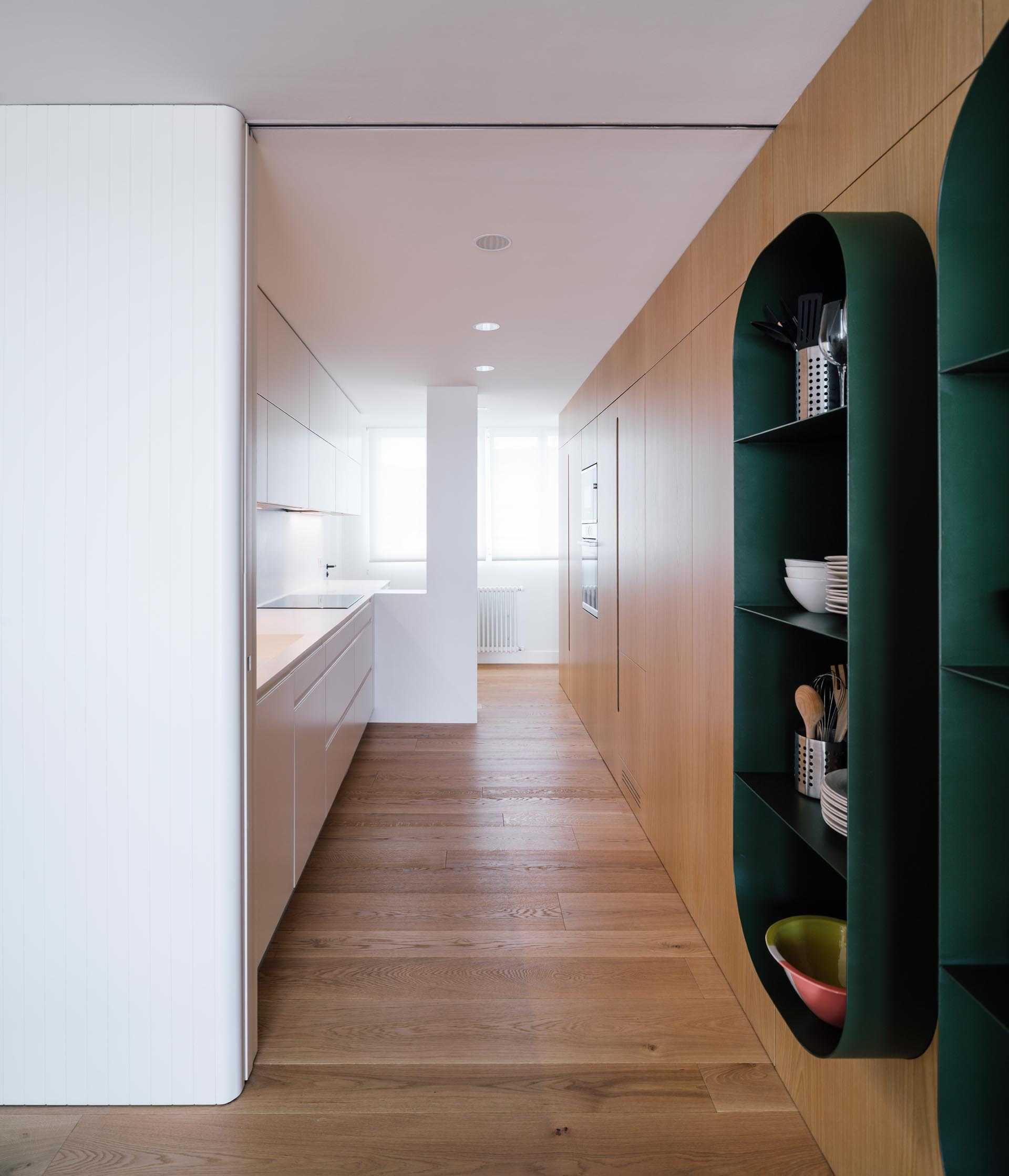 A modern white kitchen with a wall of storage made from wood.