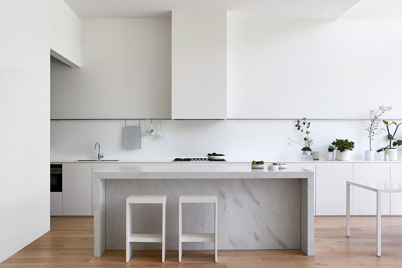 A modern white kitchen and stone island.