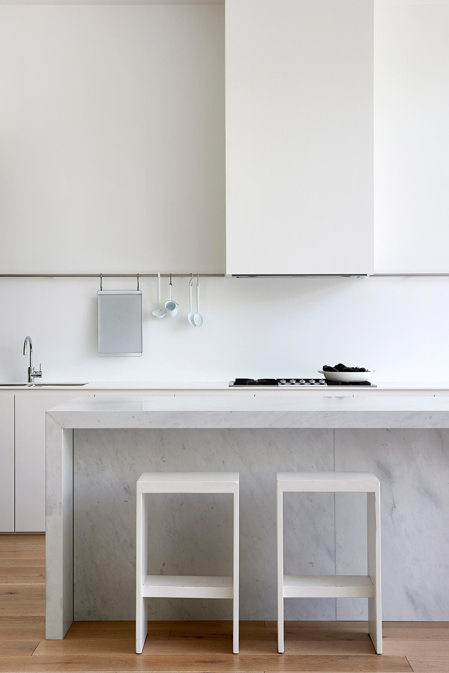 A modern white kitchen and stone island.