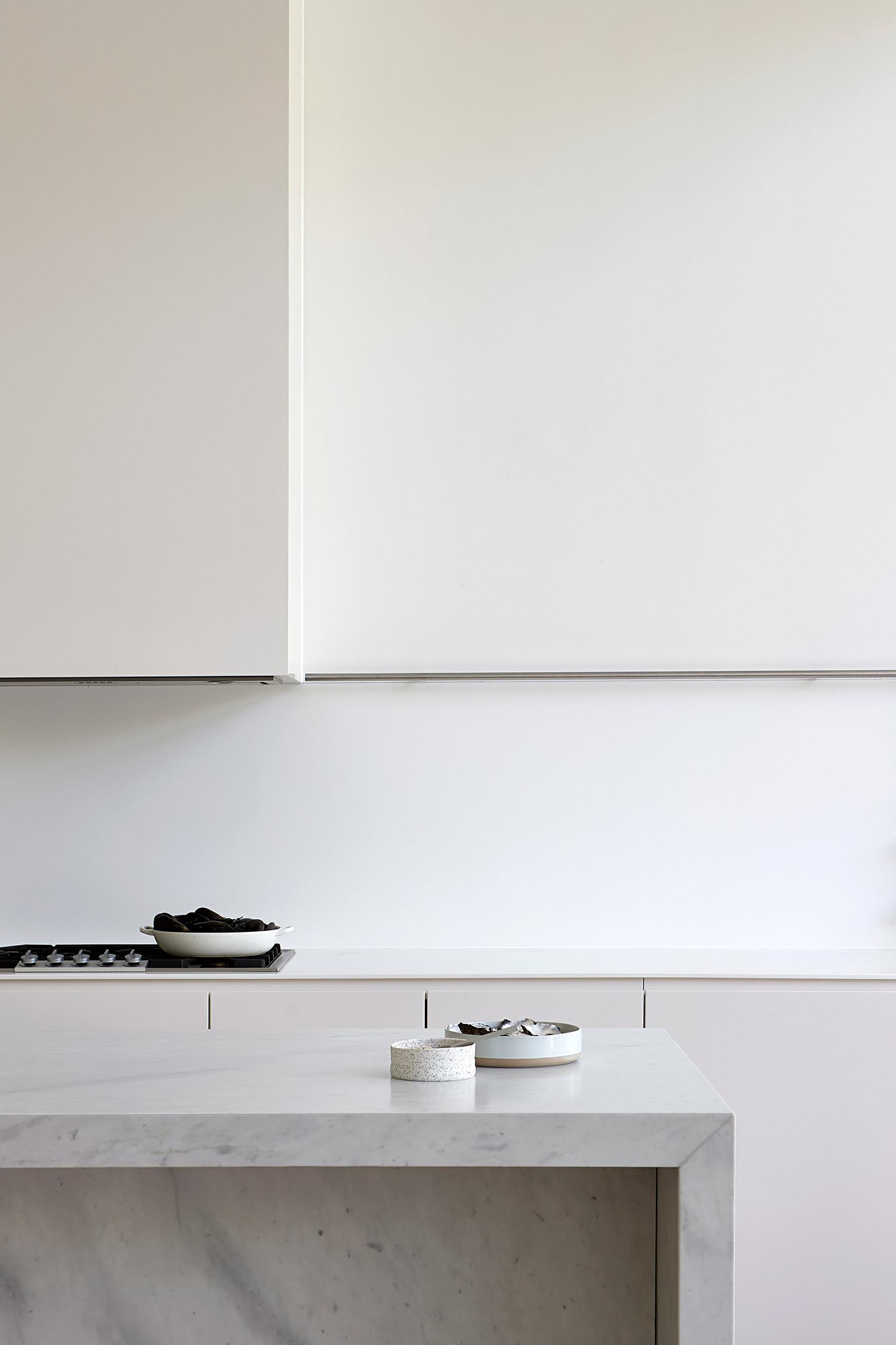 A modern white kitchen with an island.