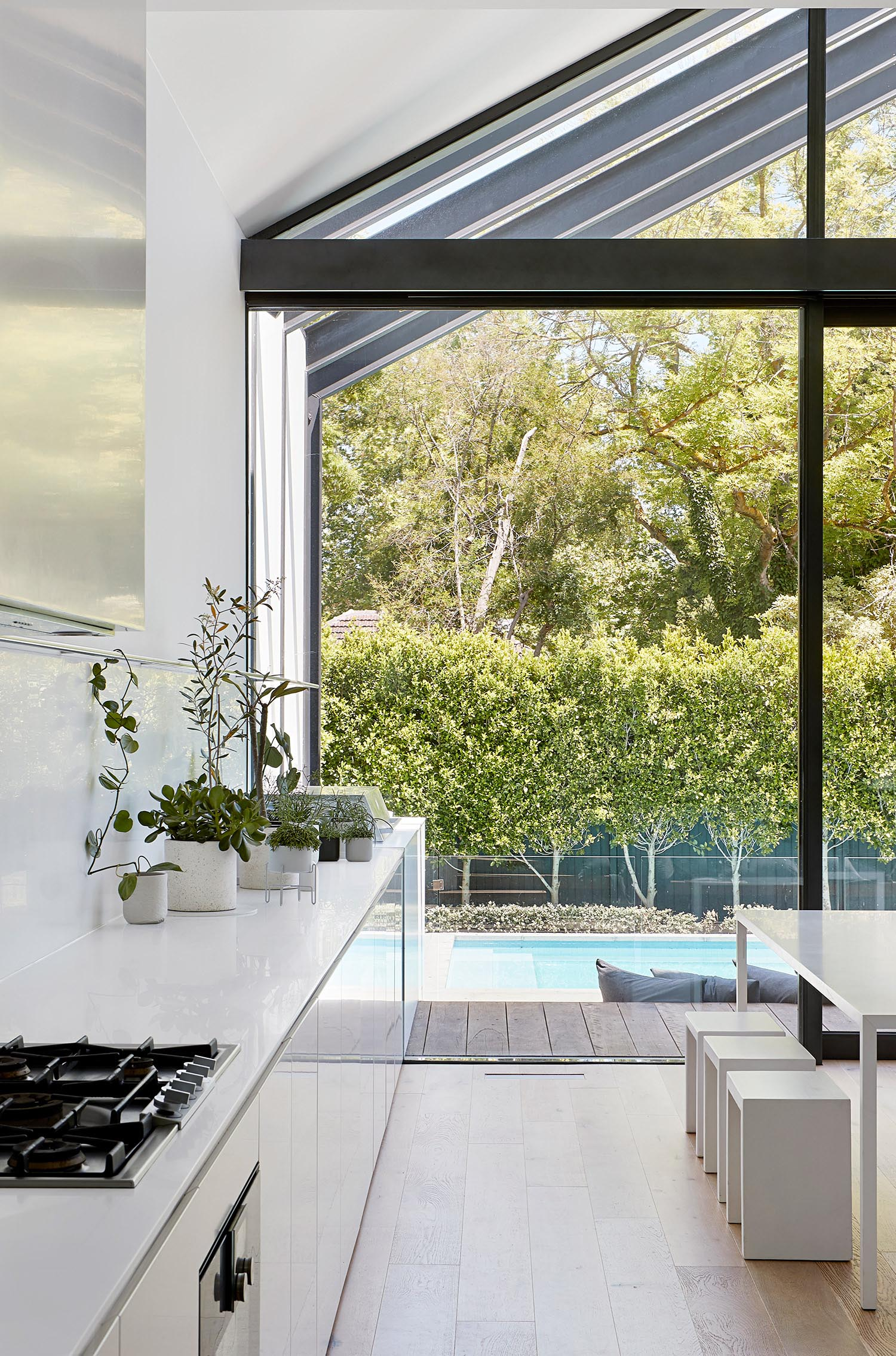 A modern white kitchen and dining room.