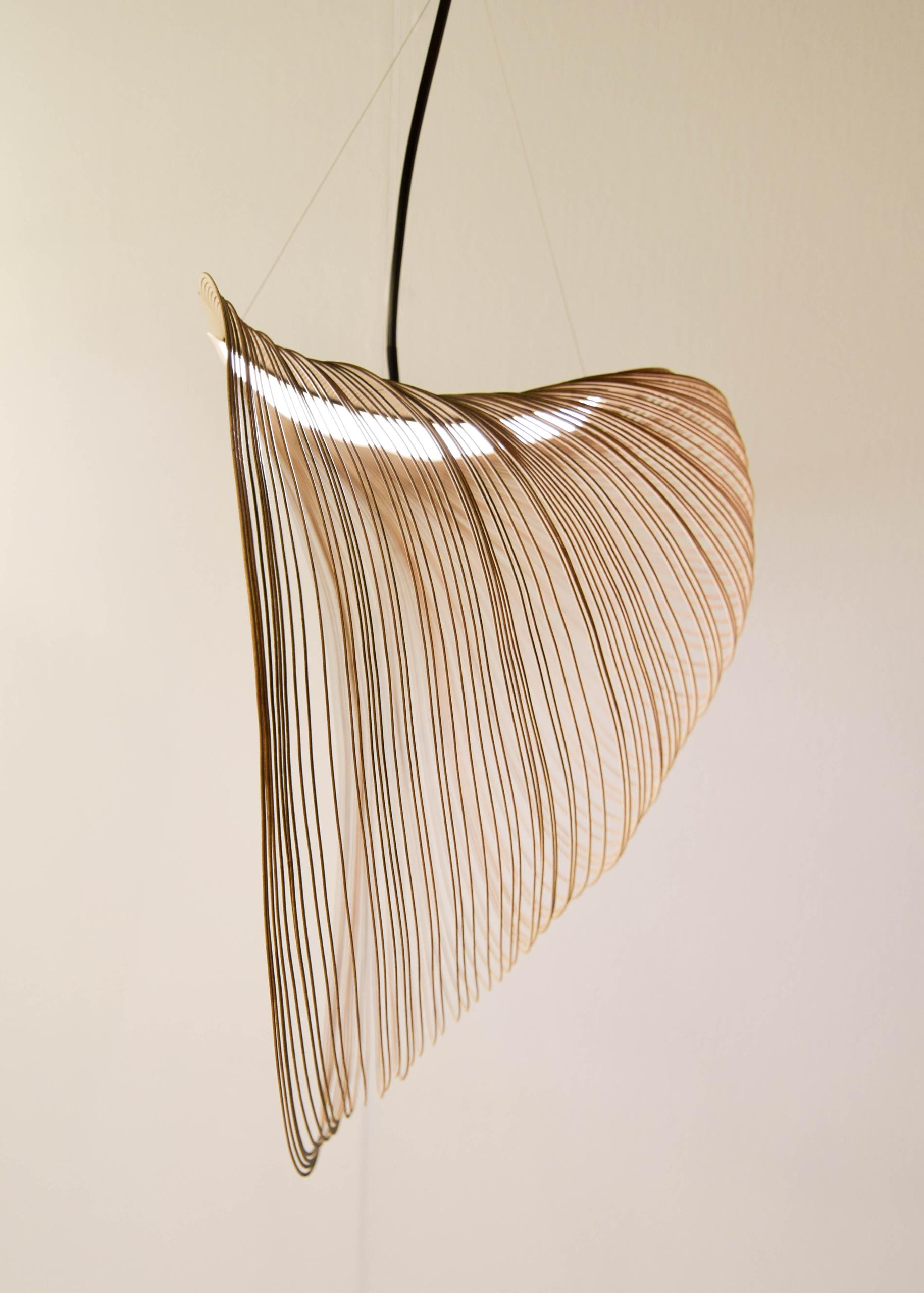 A delicate and sculptural pendant light made from laser cut wood and LEDs.