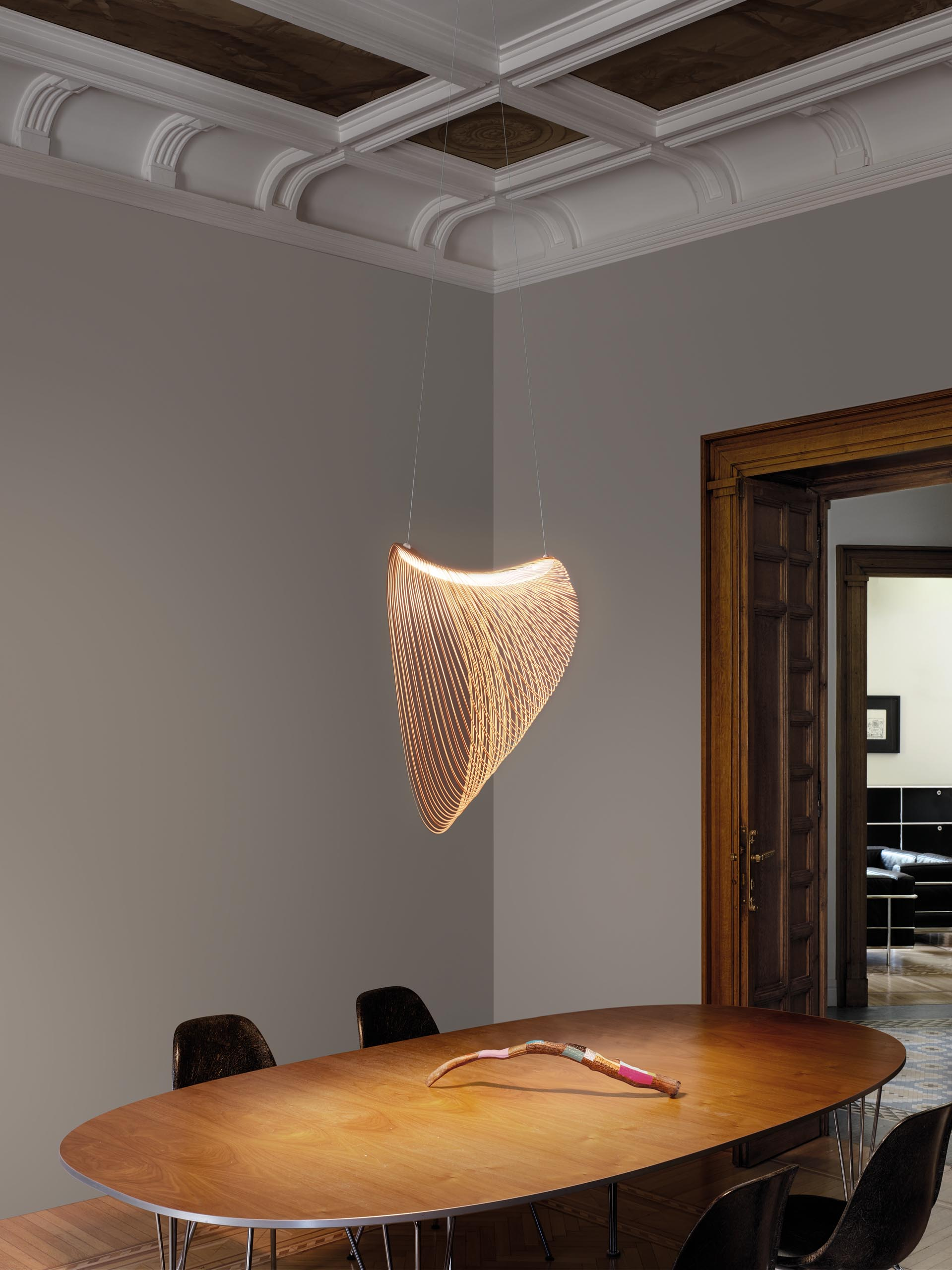 A delicate pendant light made from laser cut wood and LEDs hangs above a dining table..