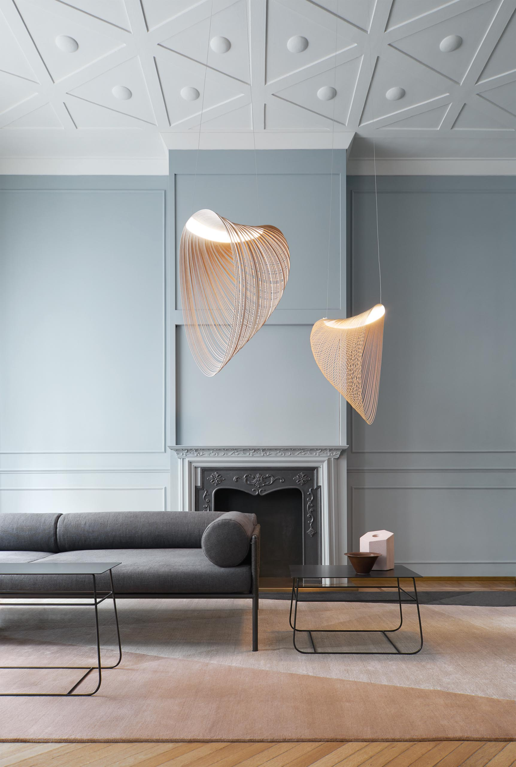 A pair of delicate and sculptural pendant light hang in a living room.