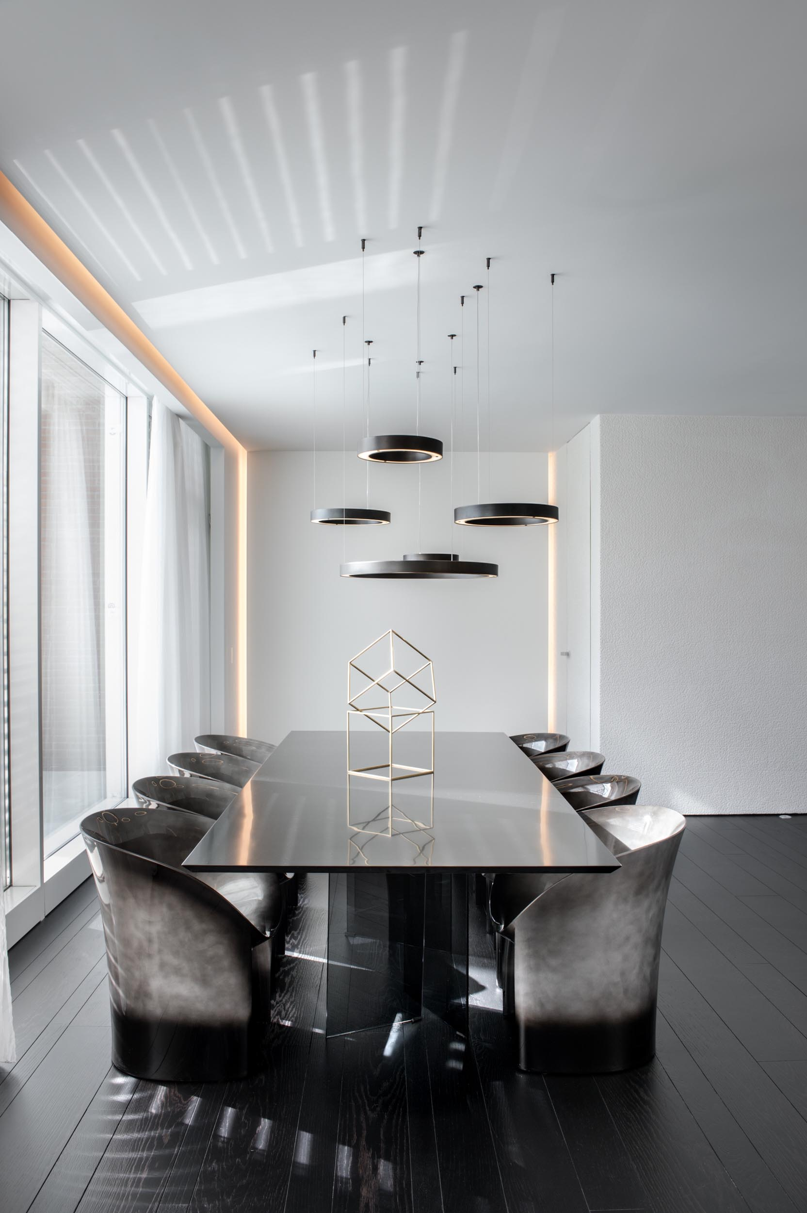 A modern dining room with circular pendant lights hanging above the black dining table, while the surrounding dining chairs are dark with a silvery element.