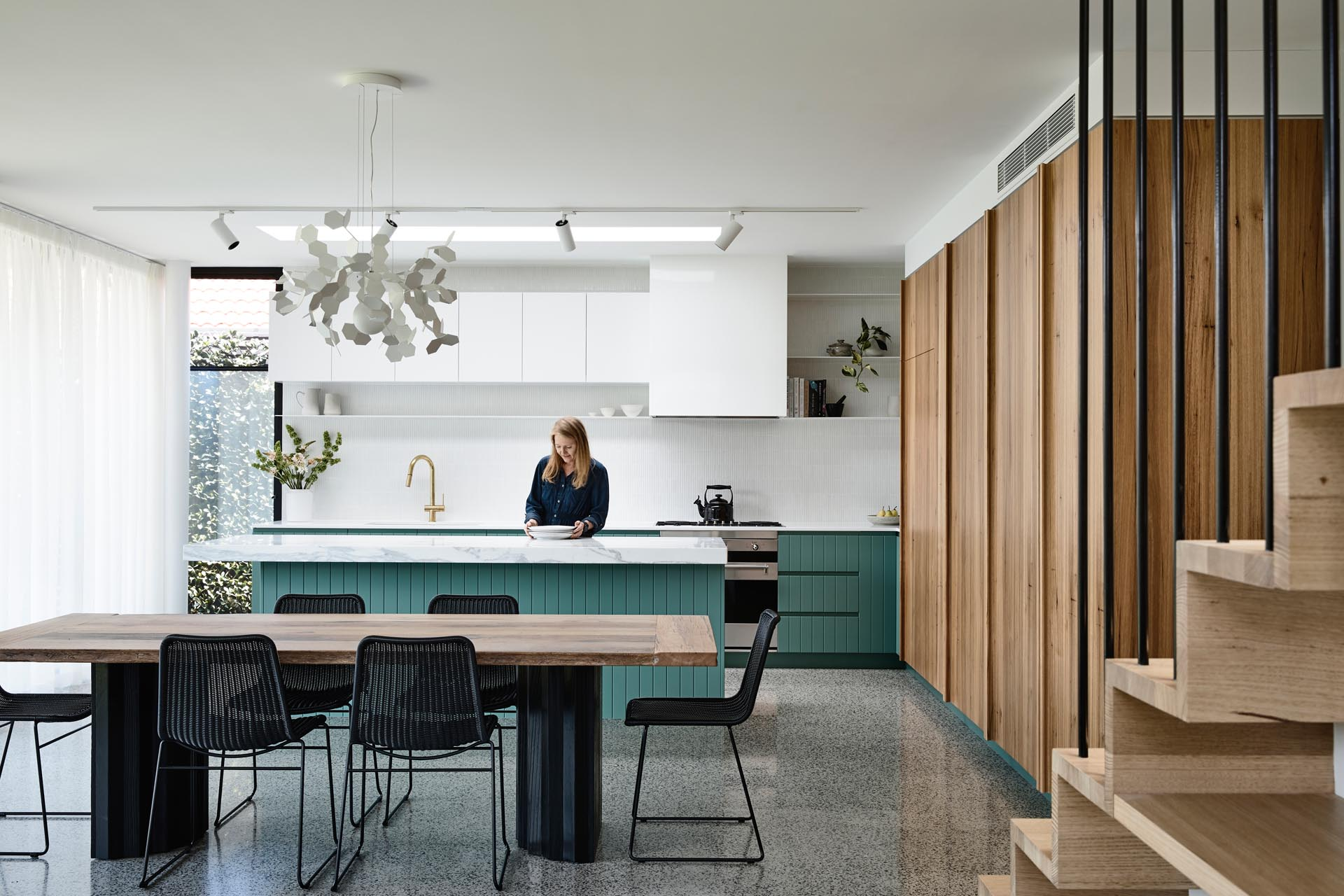 A modern interior with a dining area that has a large wood table with a black base that matches the black chairs, while in the kitchen, green cabinets add a colorful accent to the white countertops and upper cabinets.