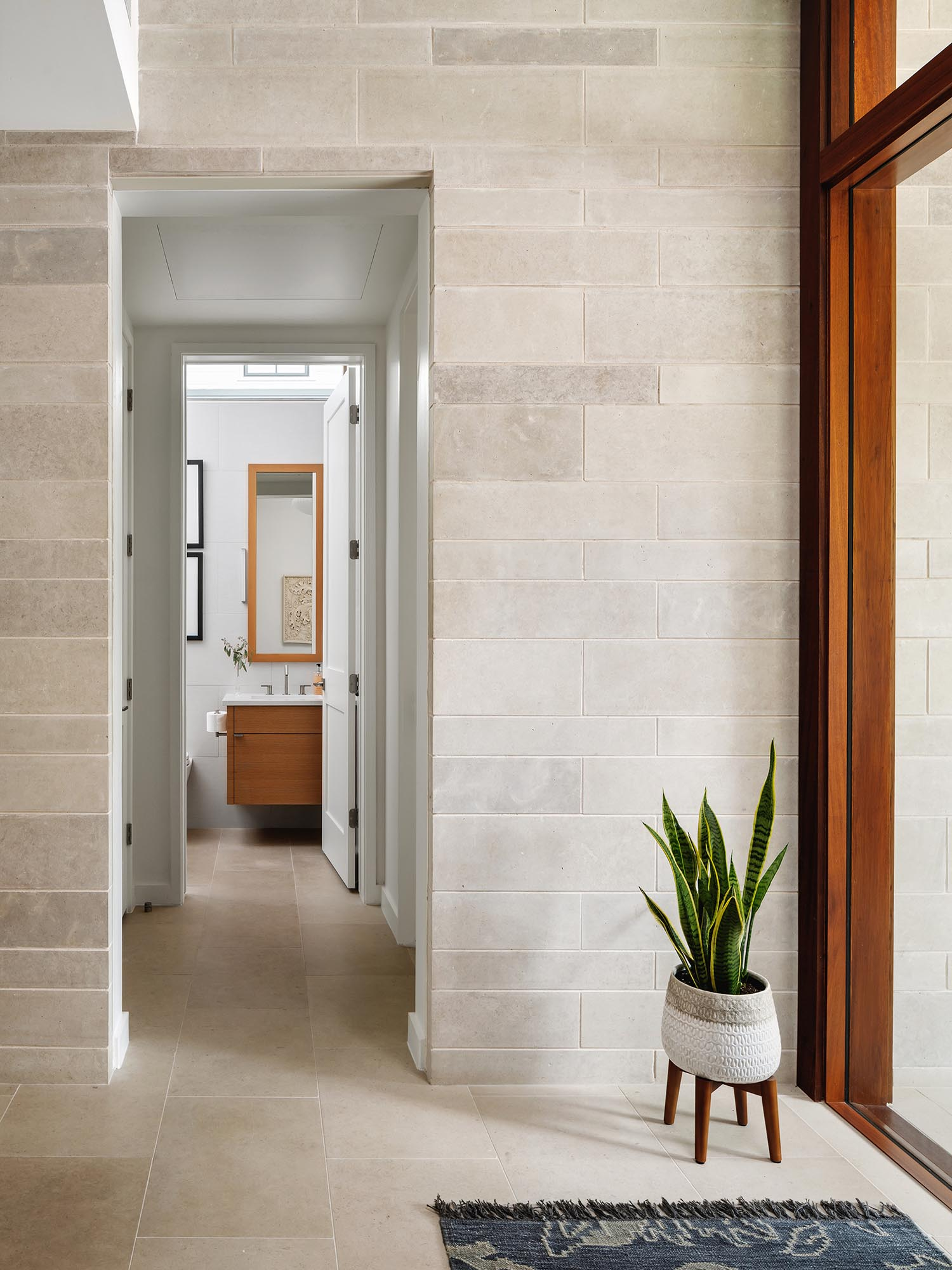 The Texas Lueders limestone on the exterior of the home continues through to the entryway.