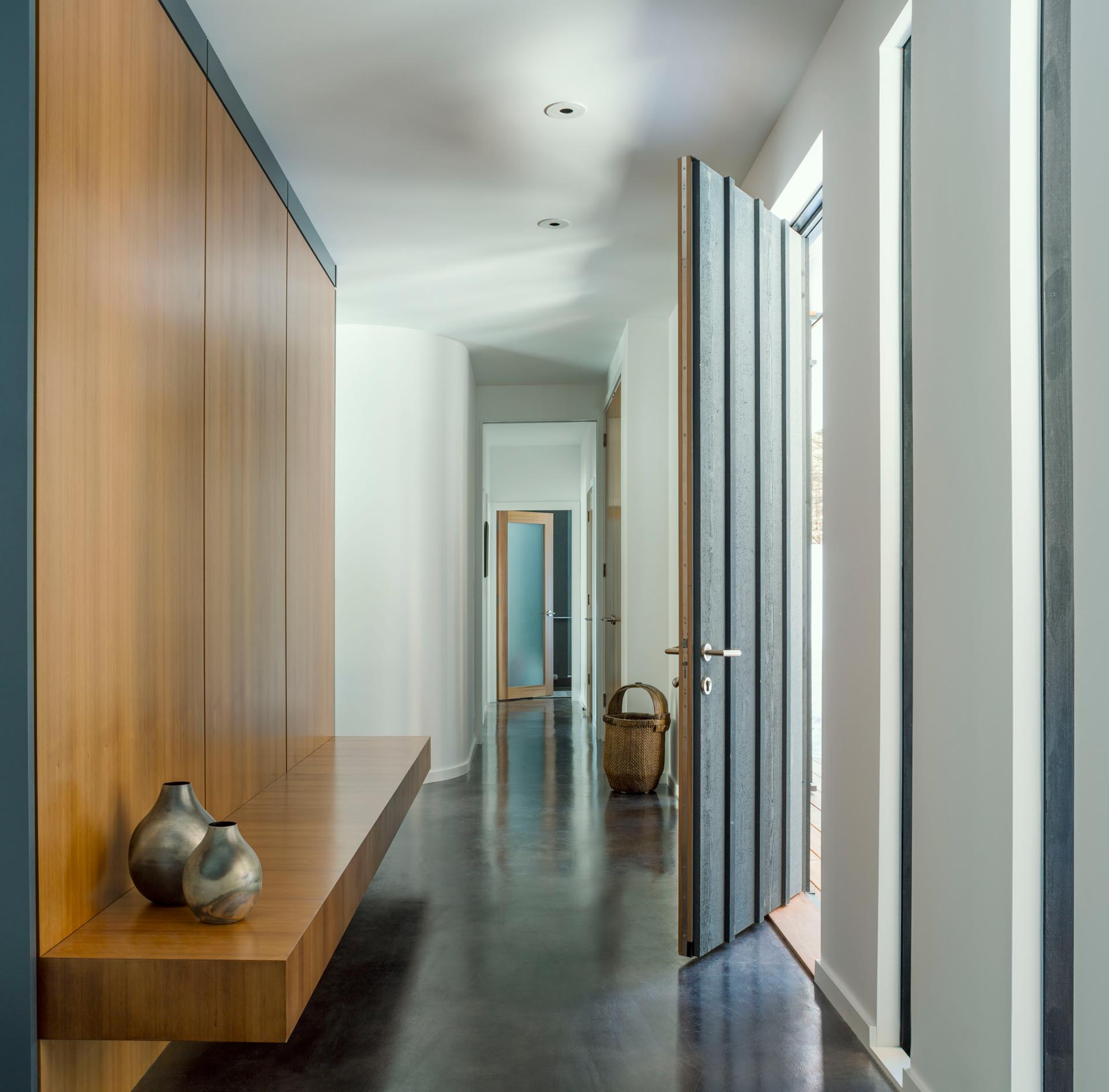 A modern entryway with polished concrete floor, a wood accent wall, and a floating wood bench.