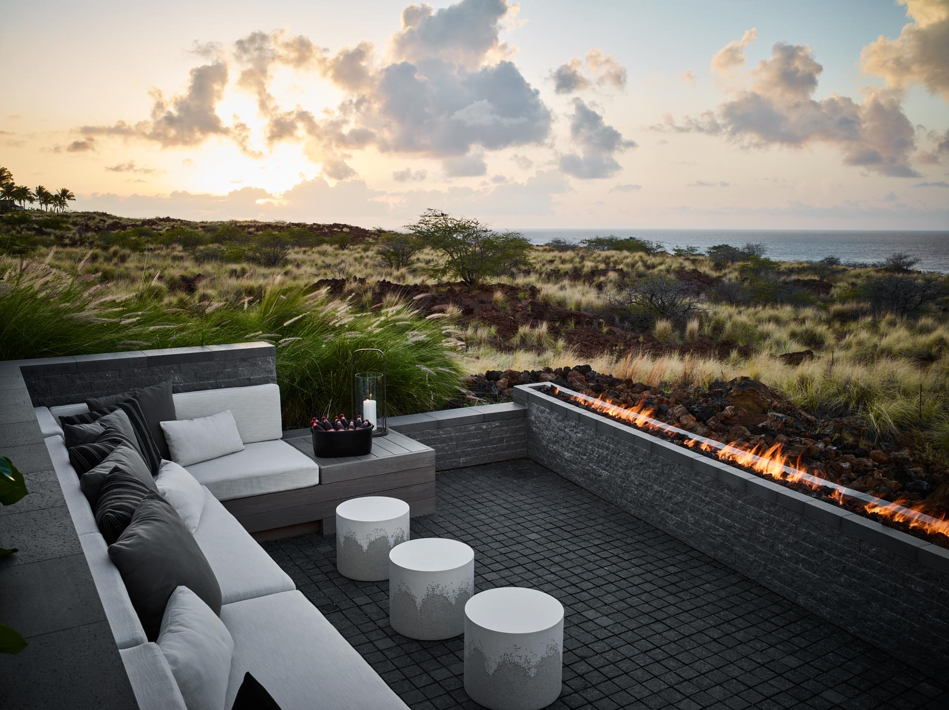 A modern outdoor lounge area with a sofa and a long fireplace.