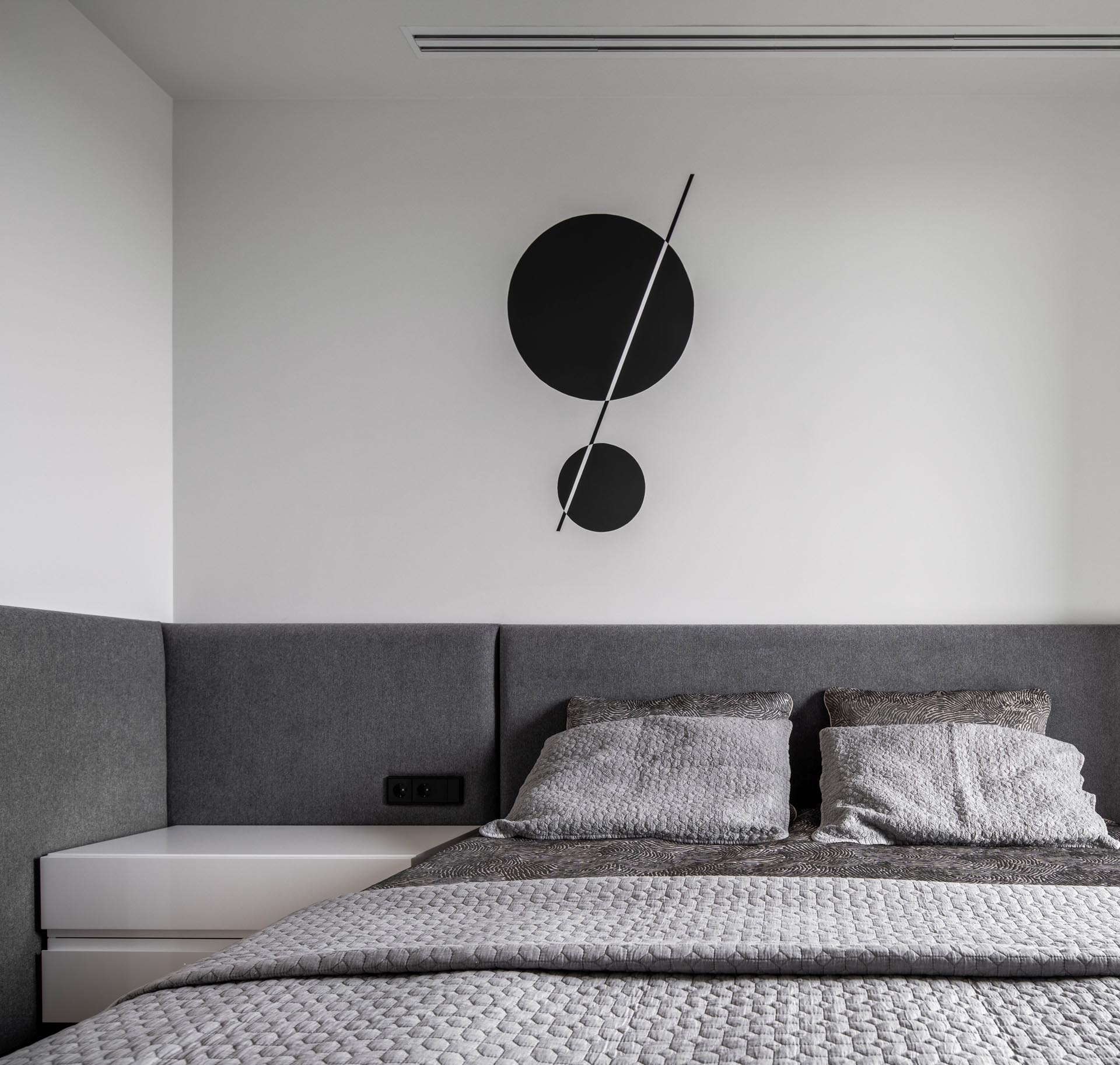 A modern hotel-inspired bedroom with gray wrap-around headboard.
