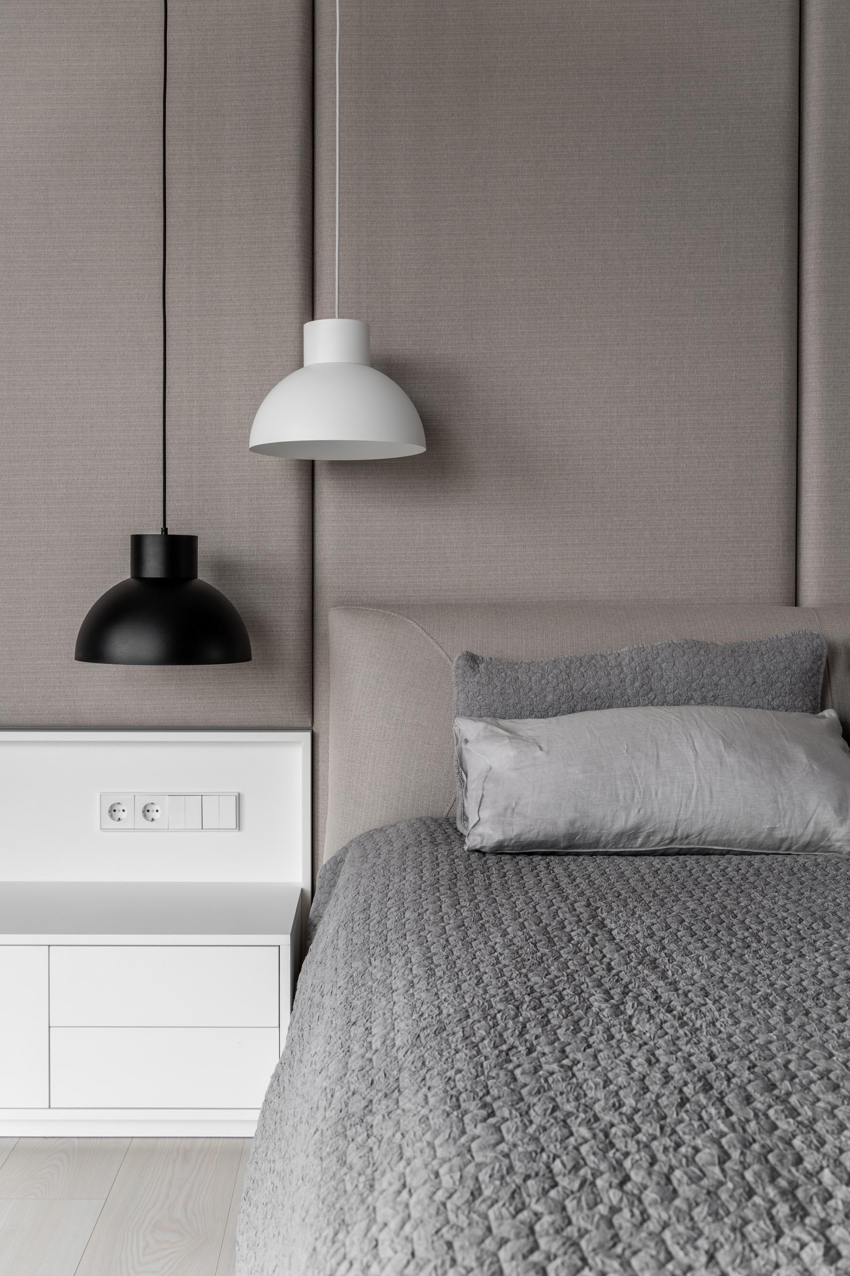A modern bedroom with a gray and beige color palette, and white and black accents.