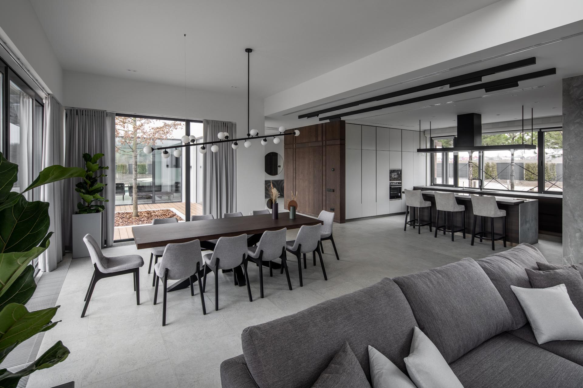 Modern open plan interior with a dining room anchored by a unique chandelier.