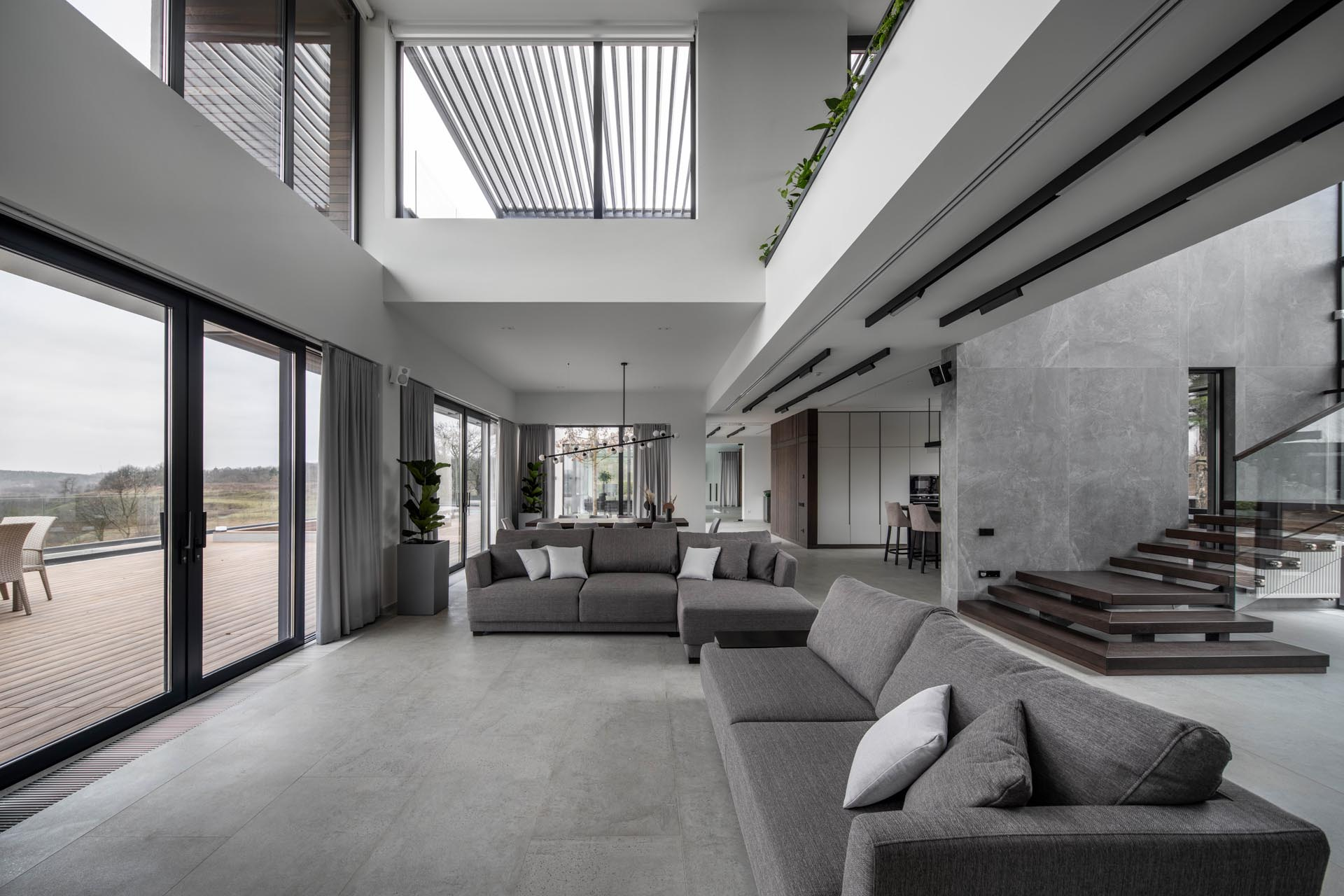 A modern living room with a gray color palette and double height ceiling.
