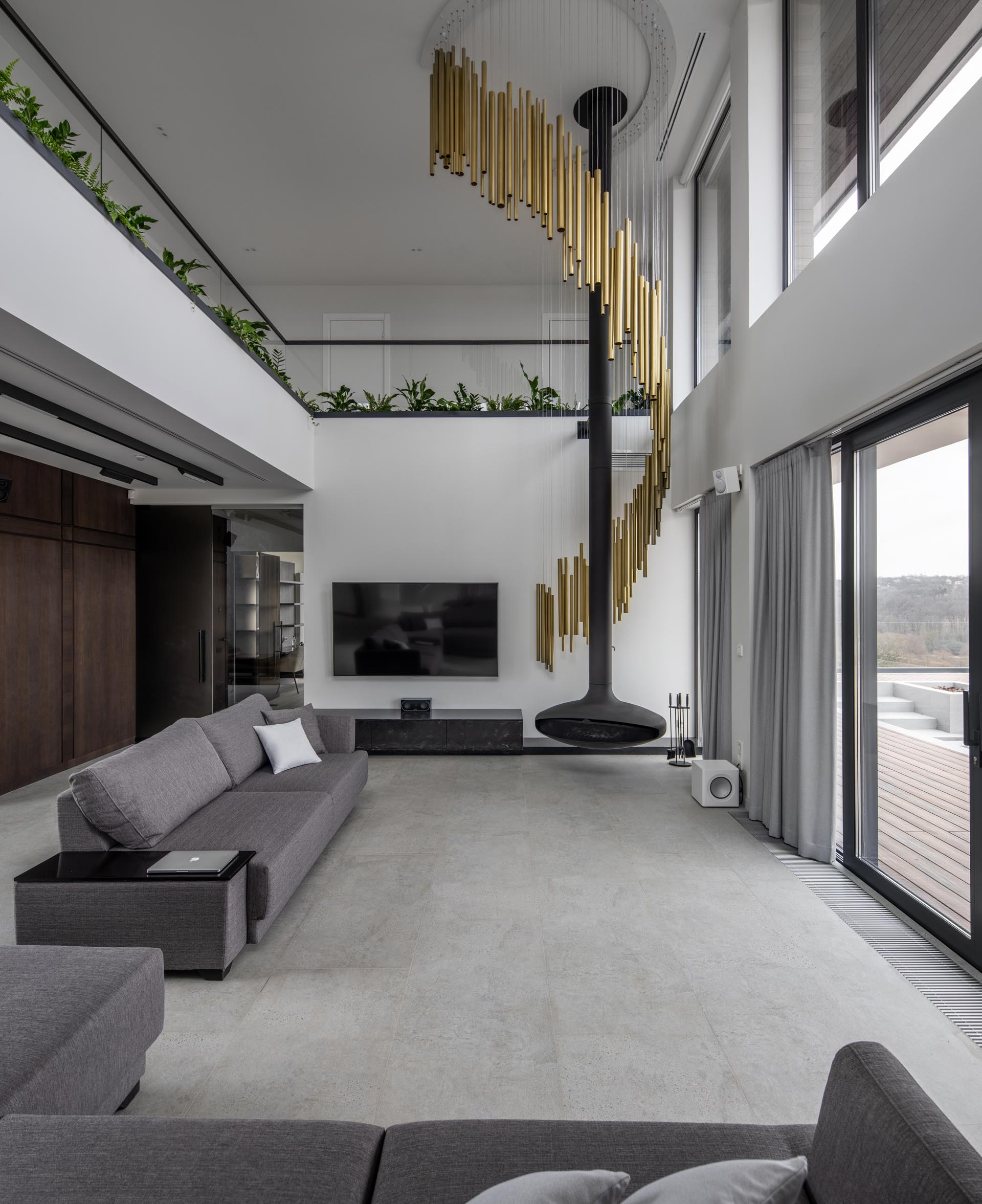 A modern living room with a suspended black fireplace and a sculptural lamp made from brass tubes whose design was inspired by wind chimes.