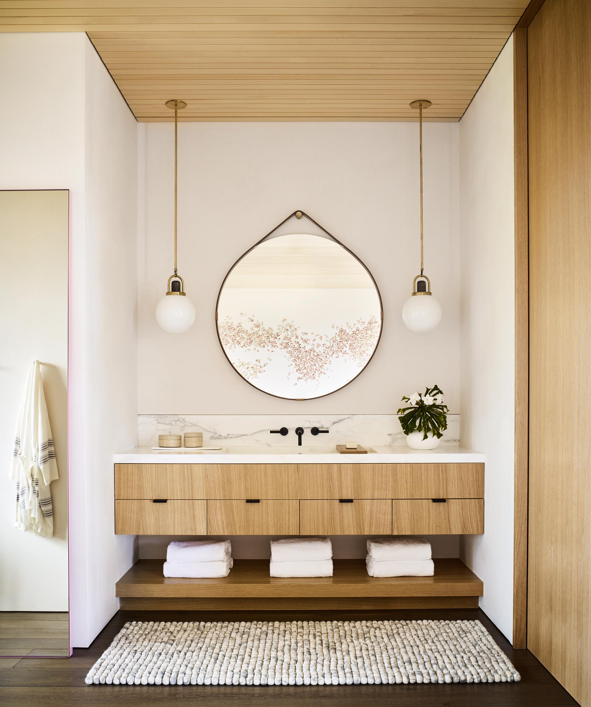 A modern bathroom with a natural color palette, a light wood vanity, and round hanging mirror.