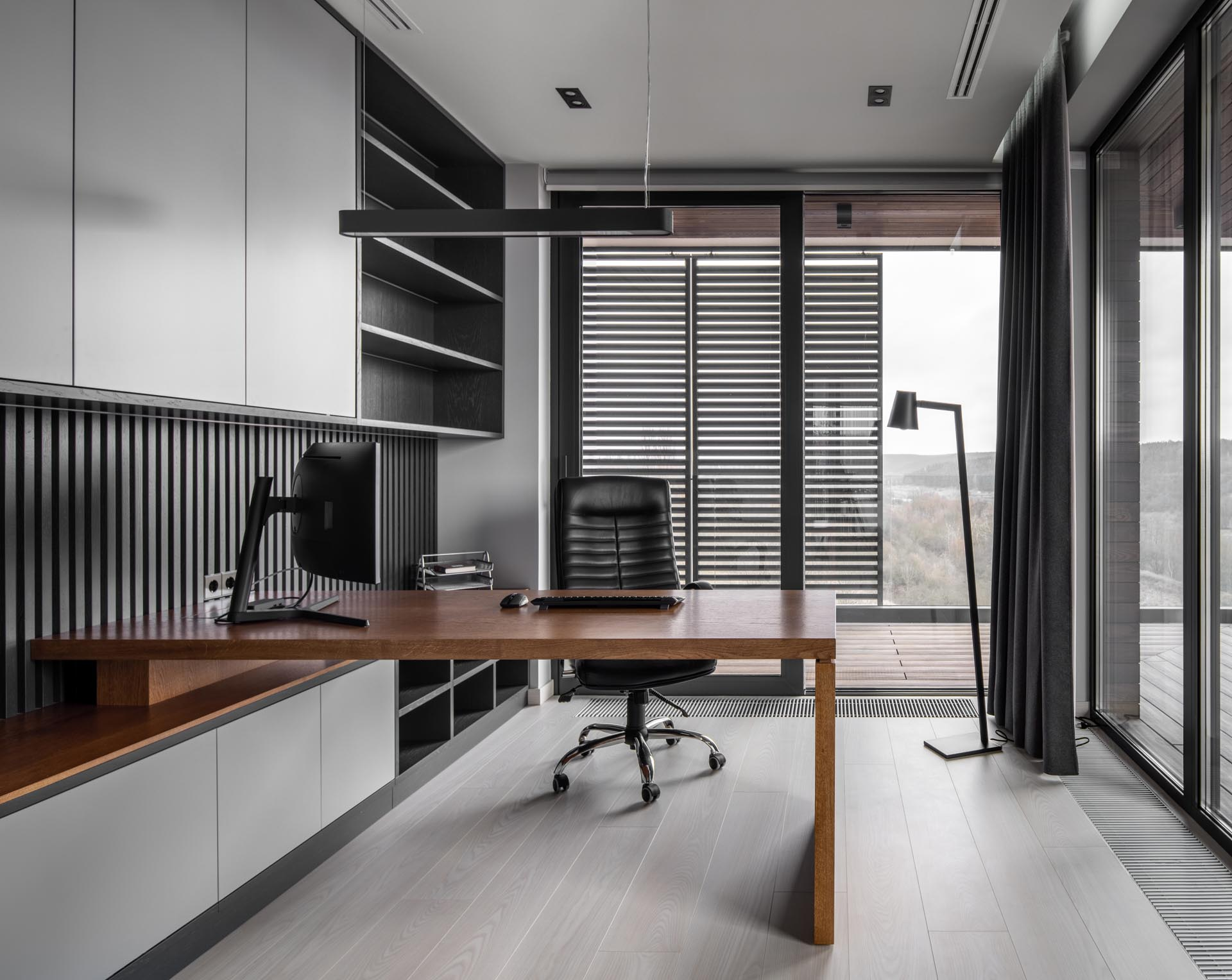 A home office has floor-to-ceiling windows and a built-in cabinetry that incorporates a wood desk.