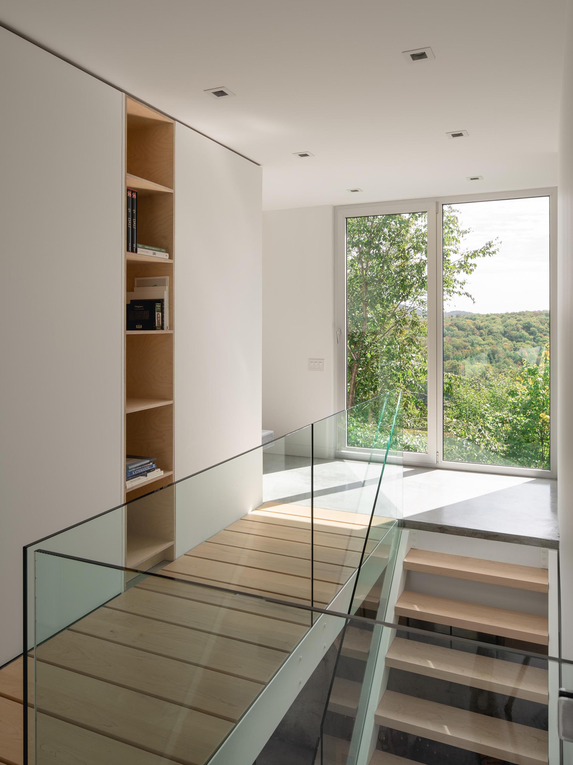 A modern home interior with wood stairs and glass handrails.