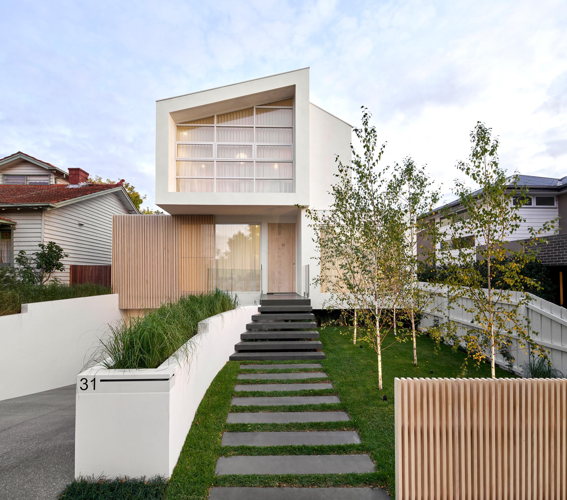 From the street, this house exterior has a path that transforms into steps that lead to the front door, while the driveway and garage are slightly hidden from view by a custom-designed planter.