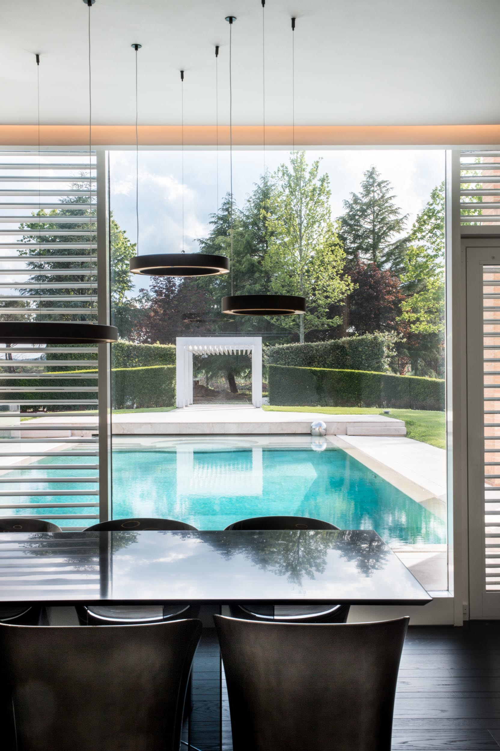 A modern dining room with a view of the pool.