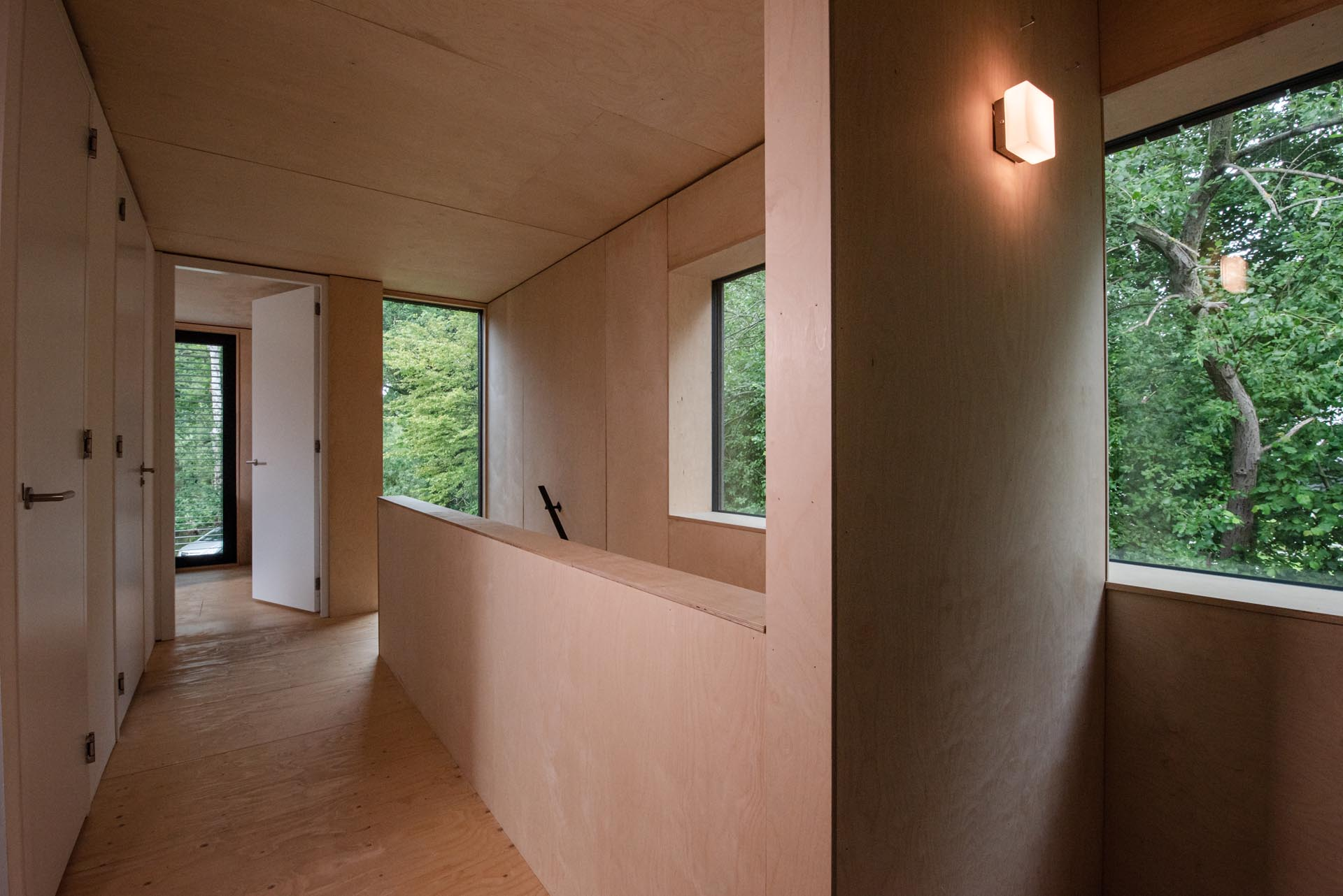 A modern home with a plywood interior and white doors.
