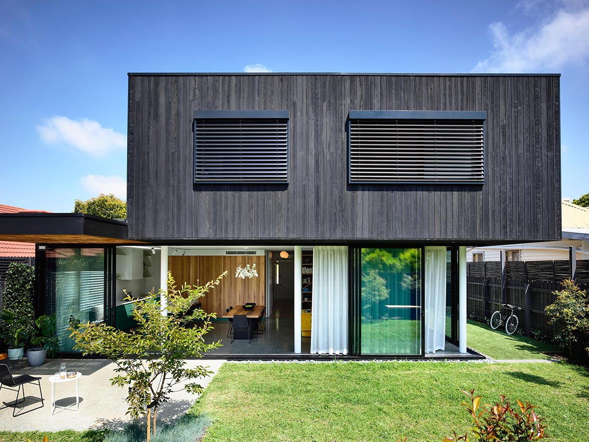 The exterior of this modern home includes a lower level with glass walls, and an upper level of charred black hardwood.