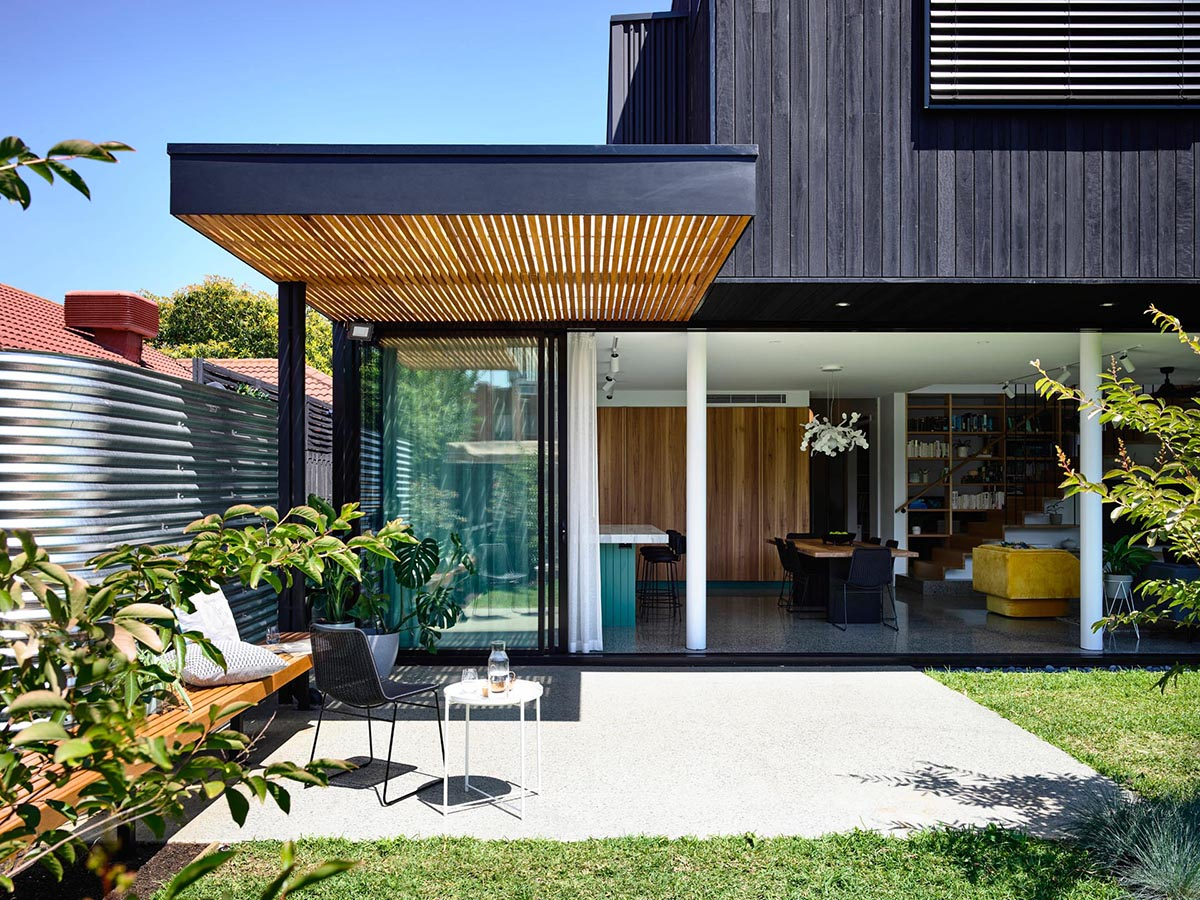 A modern home with a simple pergola that provides partial shade to a patio with a built-in bench.