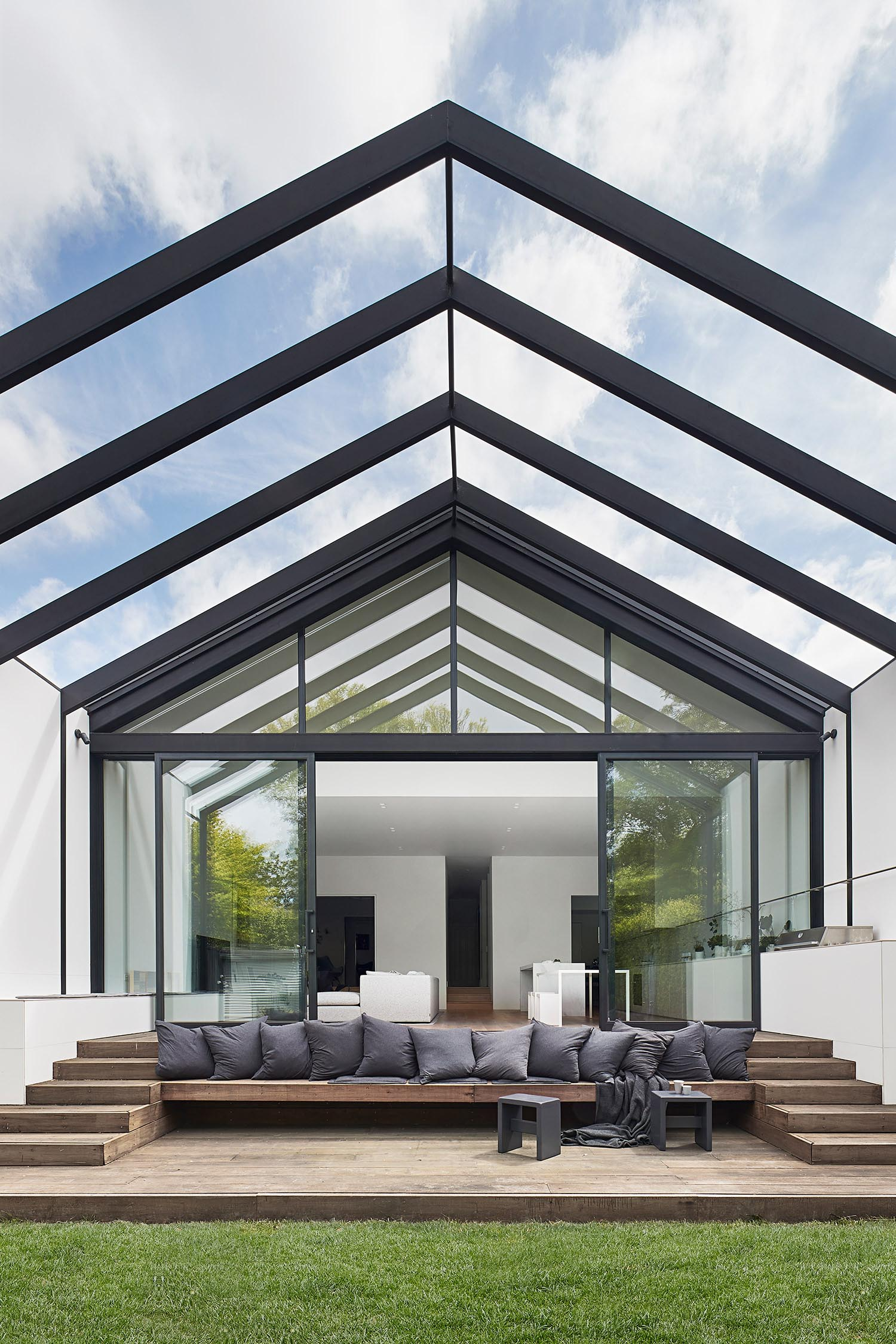 The large glass wall has been combined with black-framed sliding glass doors that create a cohesive look.