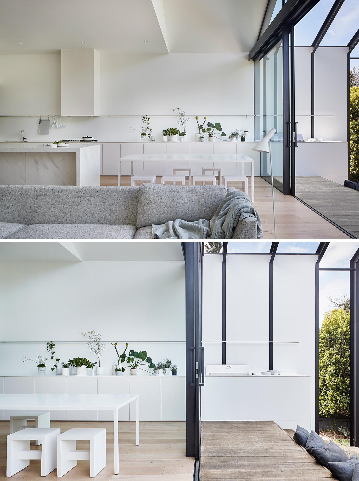 A modern home extension with a white kitchen, a large sliding glass door, and an outdoor bbq area.