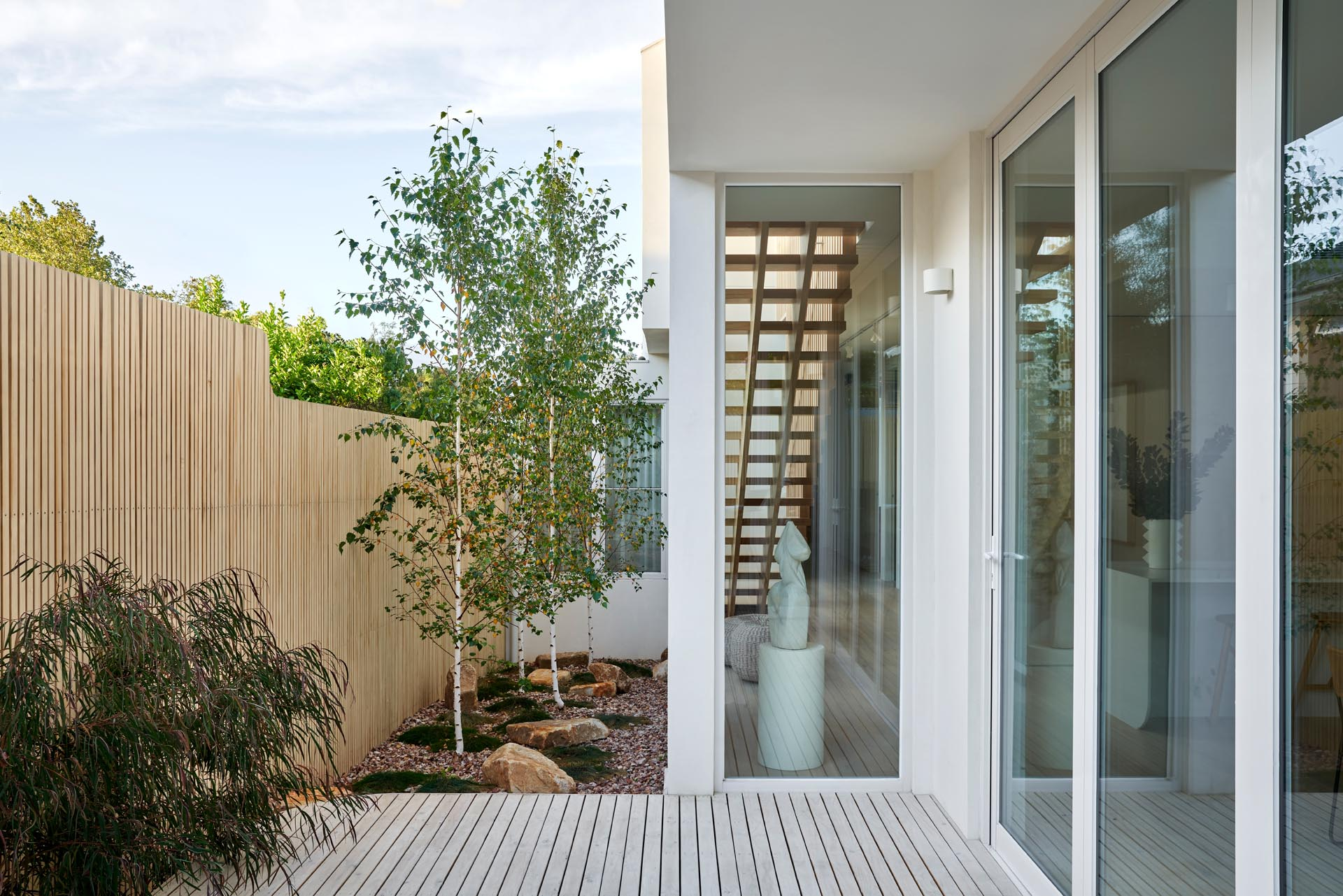 A modern house with a side garden that features a light wood fence, stones, grasses, and trees.