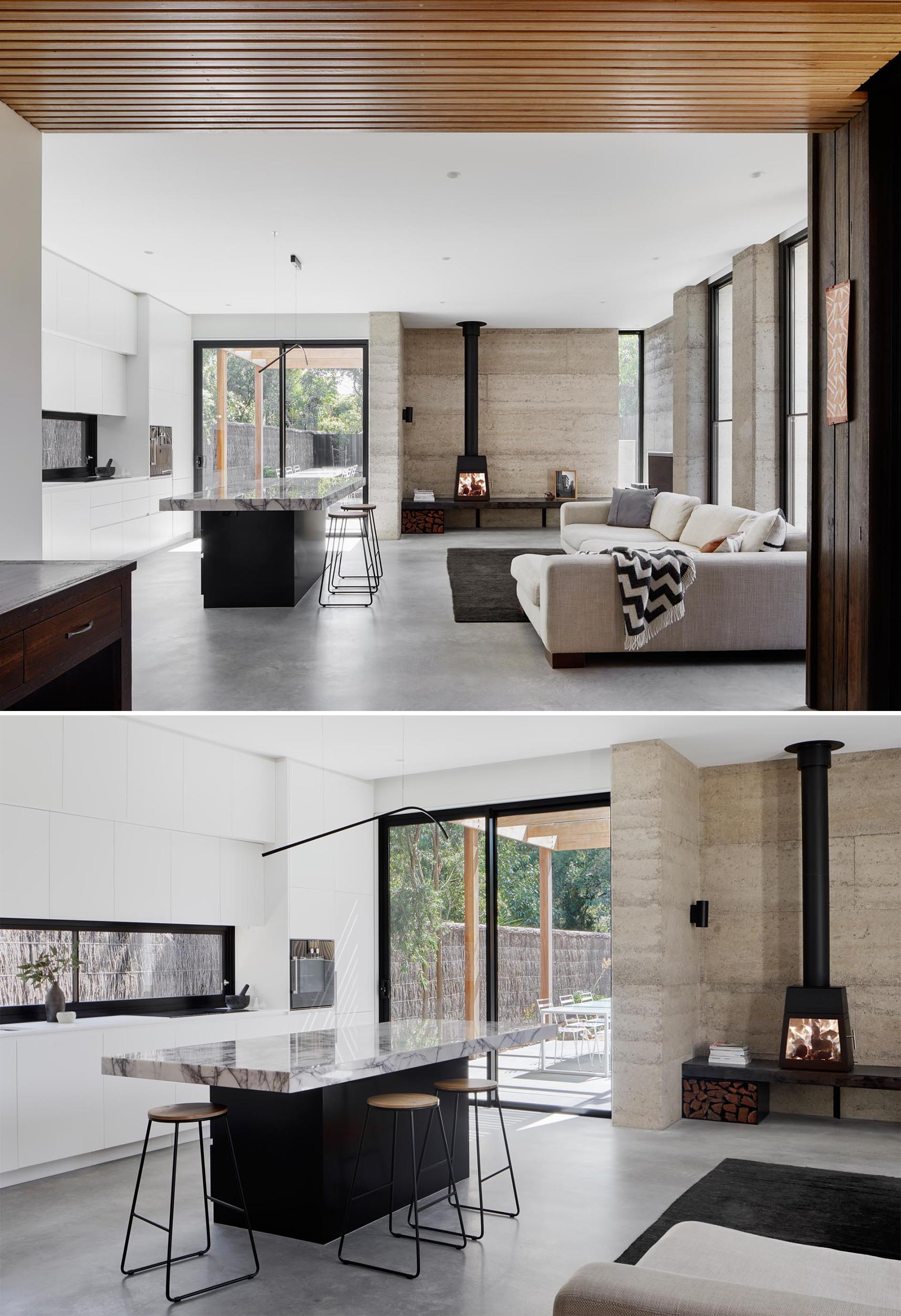 In this modern open plan living room and kitchen, there's a rammed earth wall behind the fireplace and concrete floors.