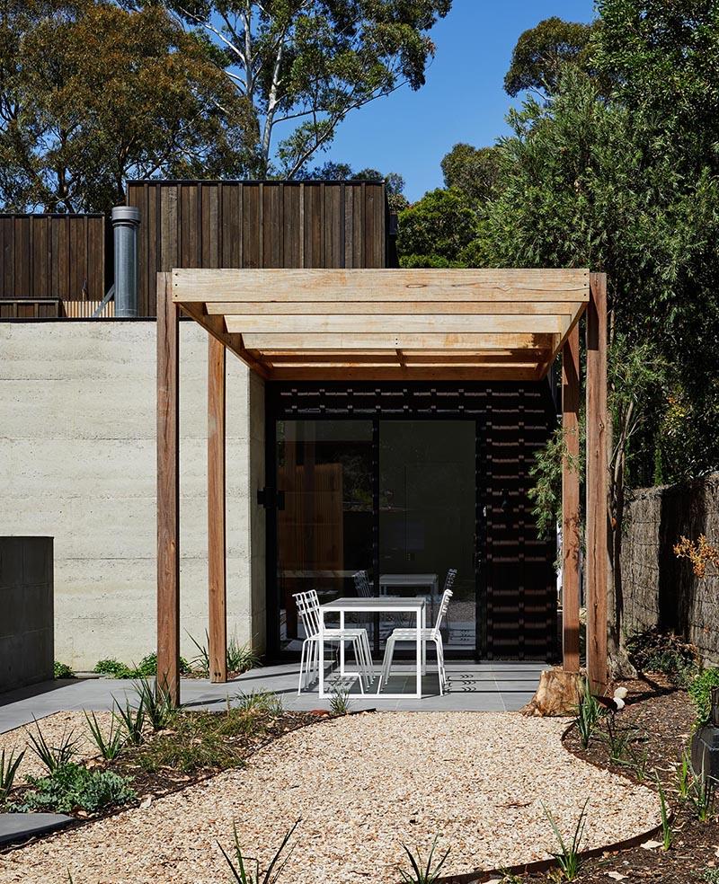 A blackbutt timber pergola leads to a landscaped garden.